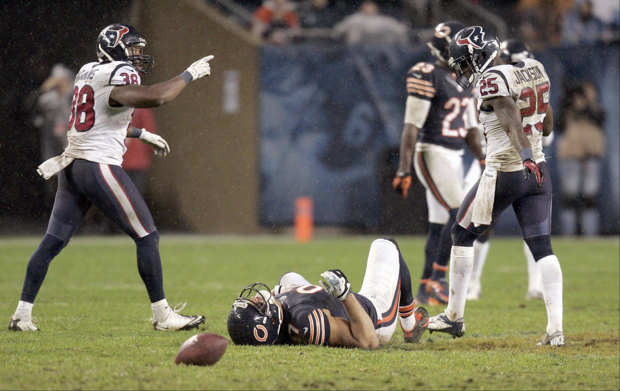 Chicago Bears tight end Kellen Davis (87) lies on the ground after missing a pass later in the fourth quarter. Houston Texans free safety Danieal Manning (38) and Kareem Jackson (25) celebrate in the background.