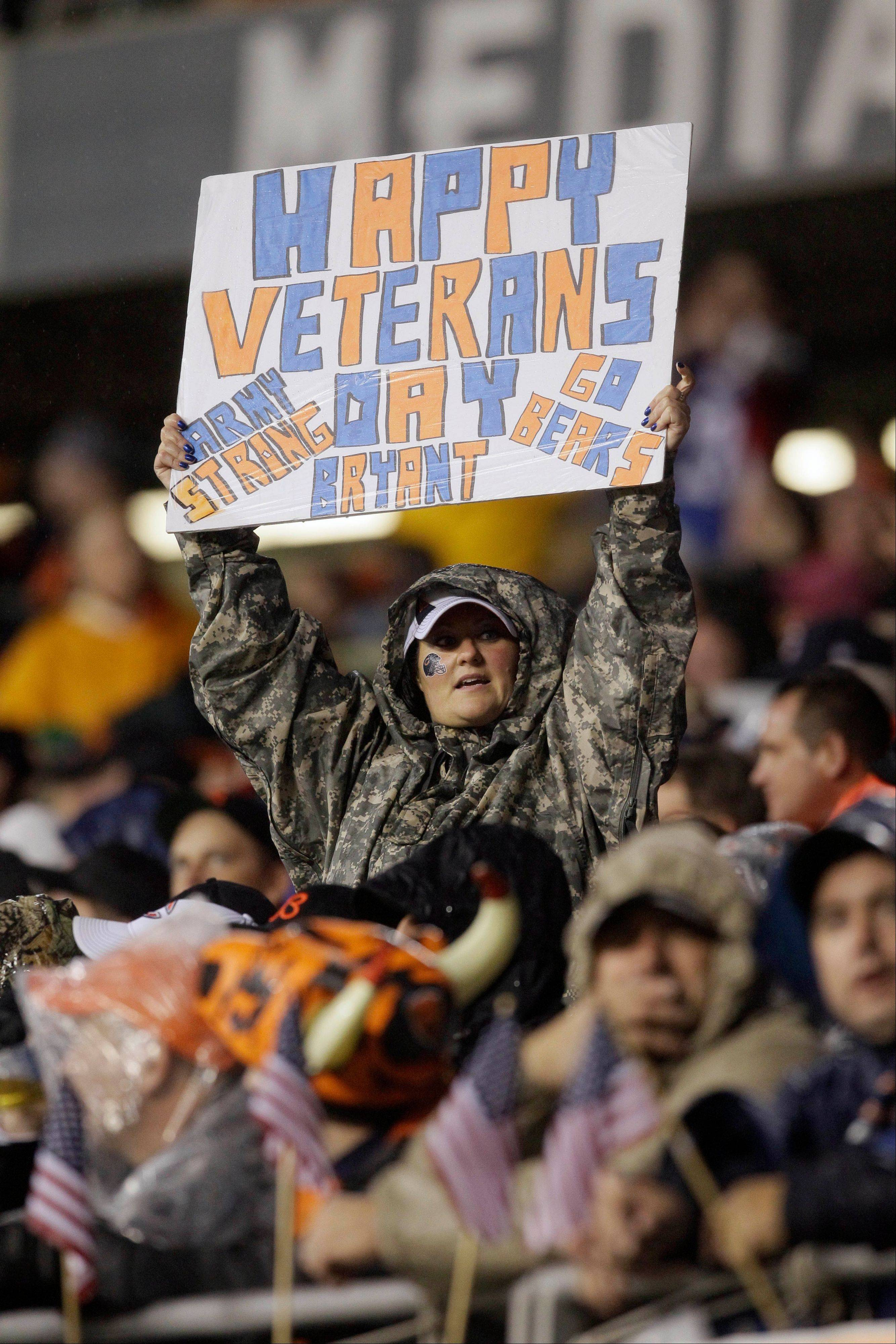 A fan holds up a sign honoring the military on Veterans Day during the NFL's Salute to Service campaign in the first half.