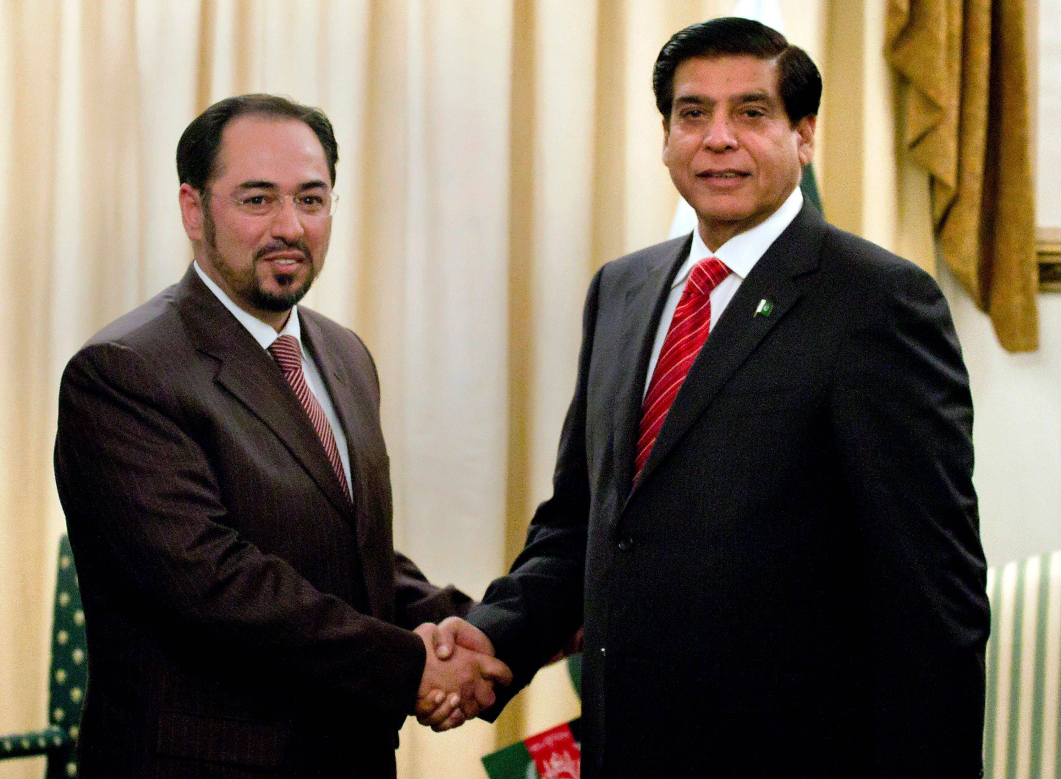Salahuddin Rabbani, left, head of Afghanistan High Peace Council, shakes hand with Pakistan�s Prime Minister Raja Pervaiz Ashraf, for the benefit of the media prior to their meeting in Islamabad, Pakistan, Monday. They were to discuss peace and the reconciliation process in Afghanistan.
