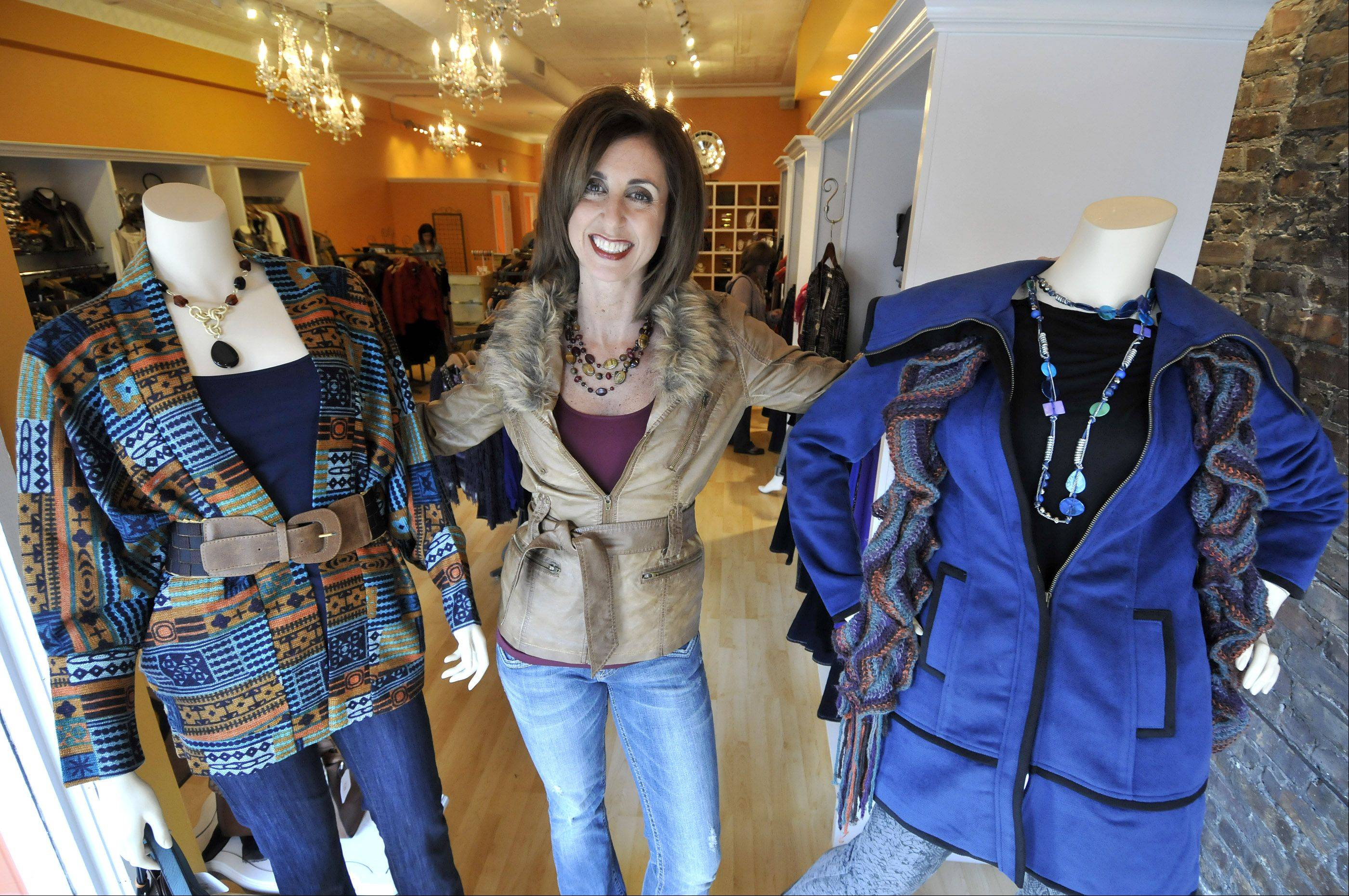 Jill Card, owner of Jeans and a Cute Top shop in Downers Grove is shown with some of her store's items. The outfit at left is a colorful jacket by Grazia with jeans by Mavi. On the right is a cobalt blue jacket with black piping by Tulle and python print pants by Mavi.