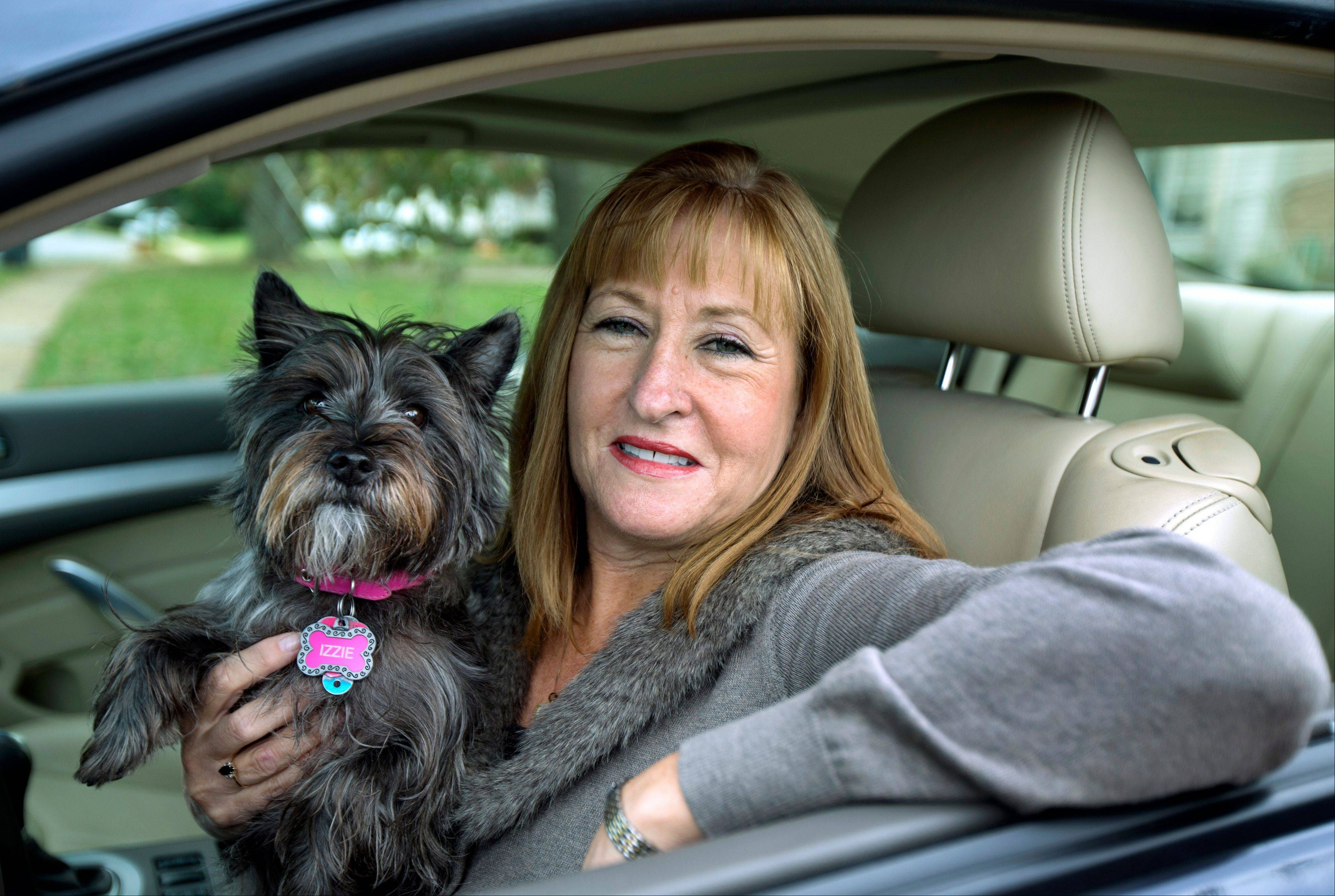 Diane Spitaliere is seen with her pet dog Izzie outside her house in Alexandria, Va. More women now have driver's licenses than men, a reversal of a longtime gender gap behind the wheel.