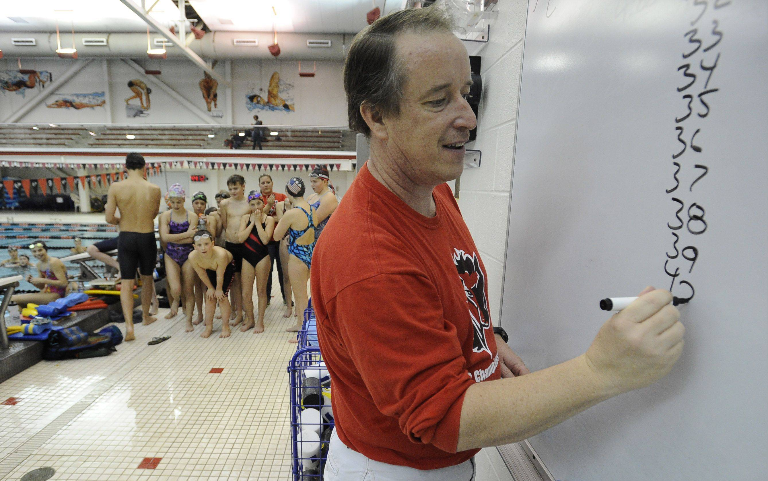 Barrington Swim Club head coach Rob Emery writes down instructions for the Barrington Swim Club and Jamaica Tornadoes during a joint practice Friday at Barrington High School.