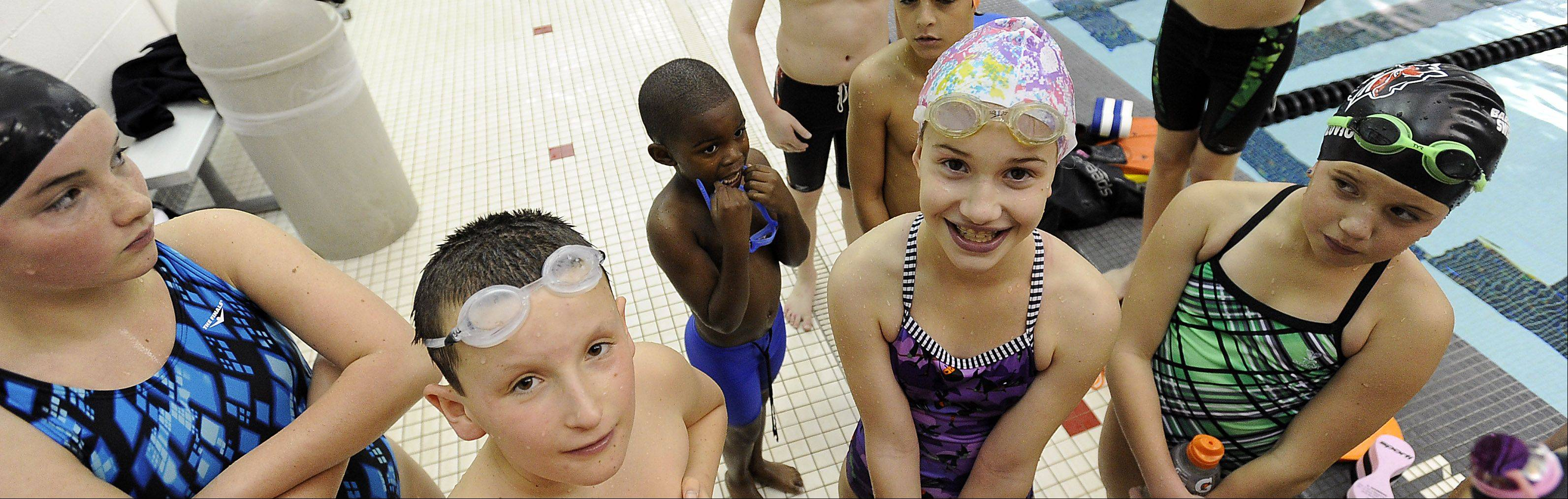Joshua Mignott, 6, of the Jamaica Tornadoes Swim Club gets slightly overshadowed as swimmers listen to instructions from a coach during practice Friday with the Barrington Swim Club at Barrington High School.