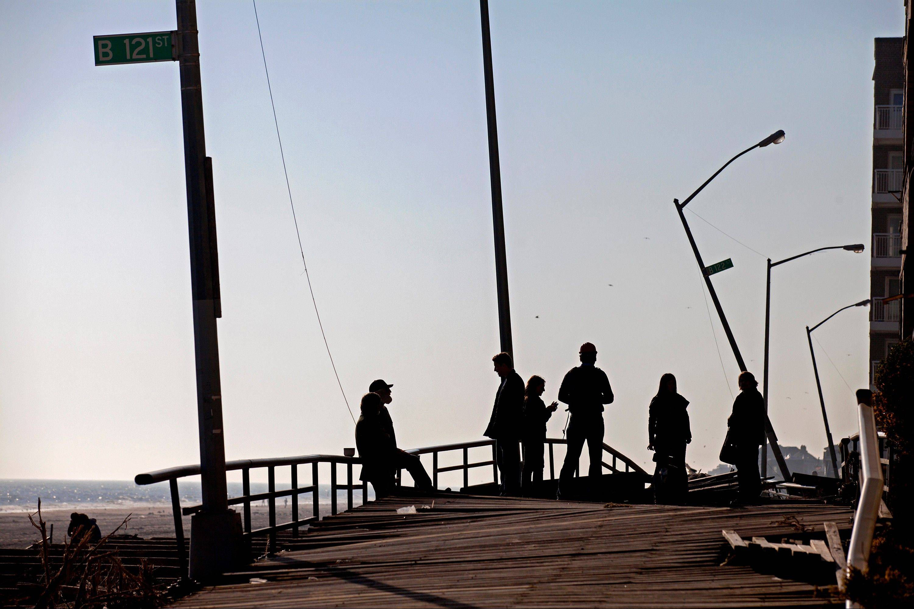 People gather on the buckled boardwalk of the Rockaway Park neighborhood of the borough of Queens, New York, Sunday, Nov. 11, 2012, in the wake of Superstorm Sandy.