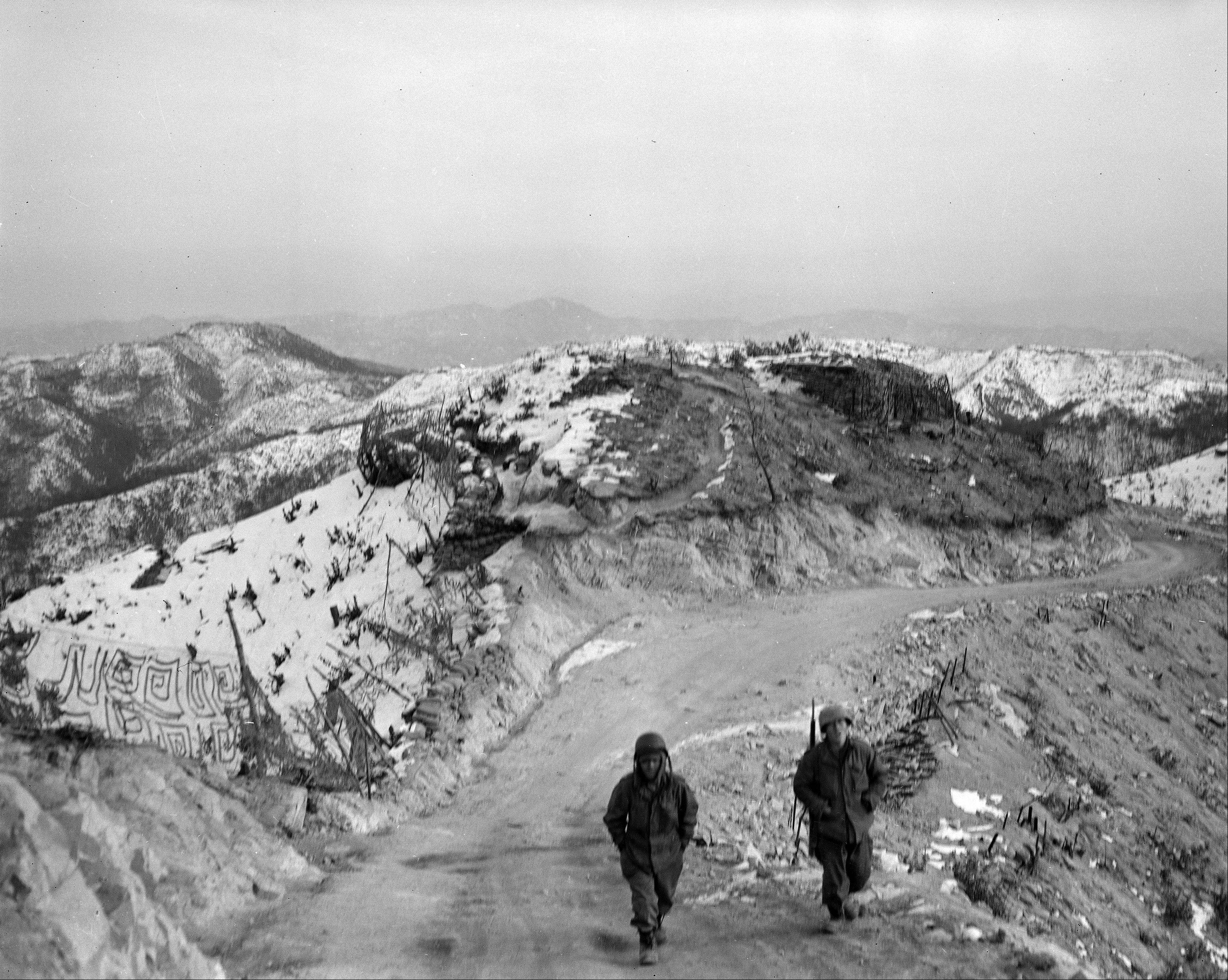 Two U.S. GIs from the 25th Division move up the cold, snow-covered road toward their front line bunker on the central front in Korea, Nov. 5, 1953.
