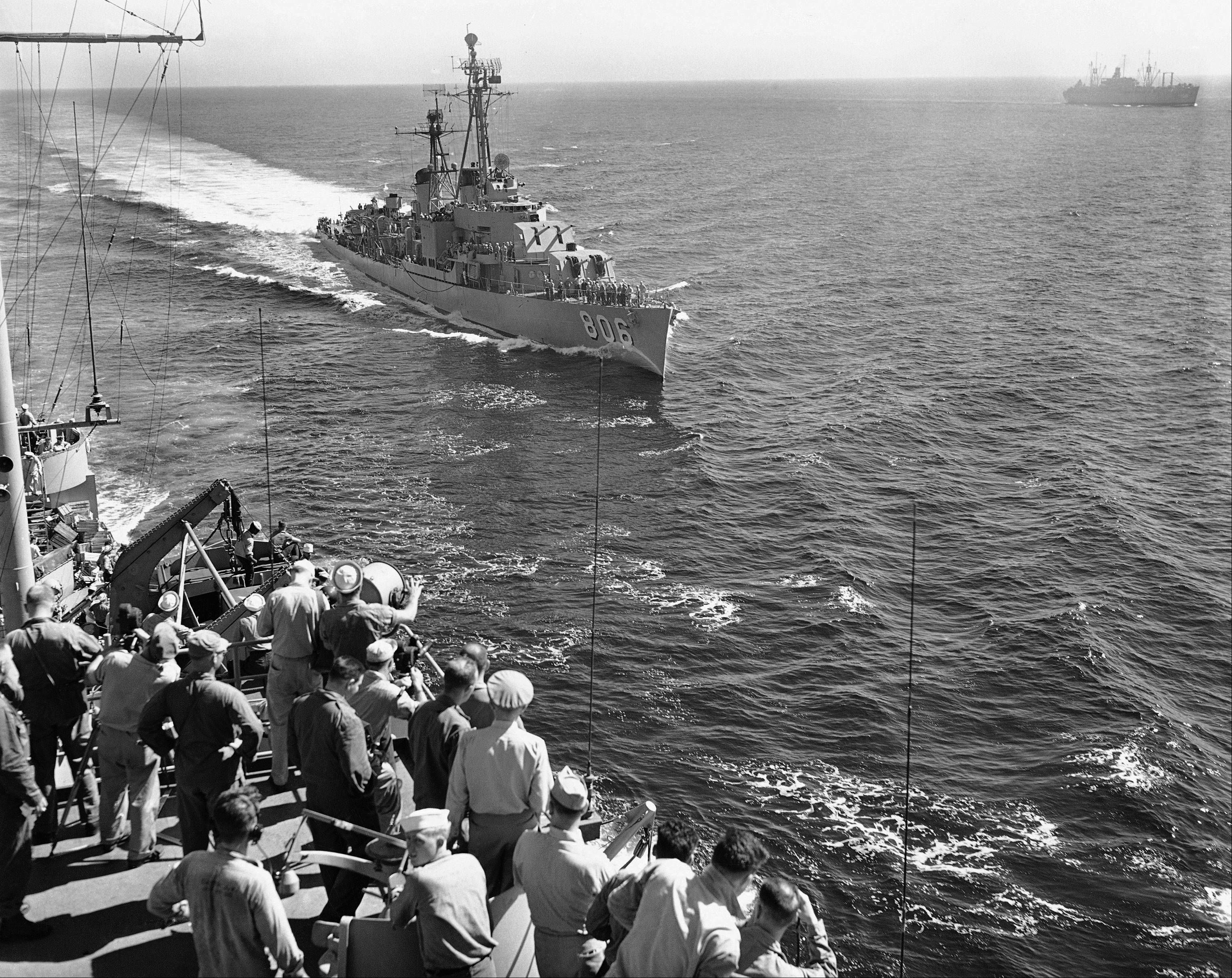 An American destroyer comes alongside a flagship to deliver a message as the convoy carries First Cavalry division from Japan to South Korea on July 21, 1950.