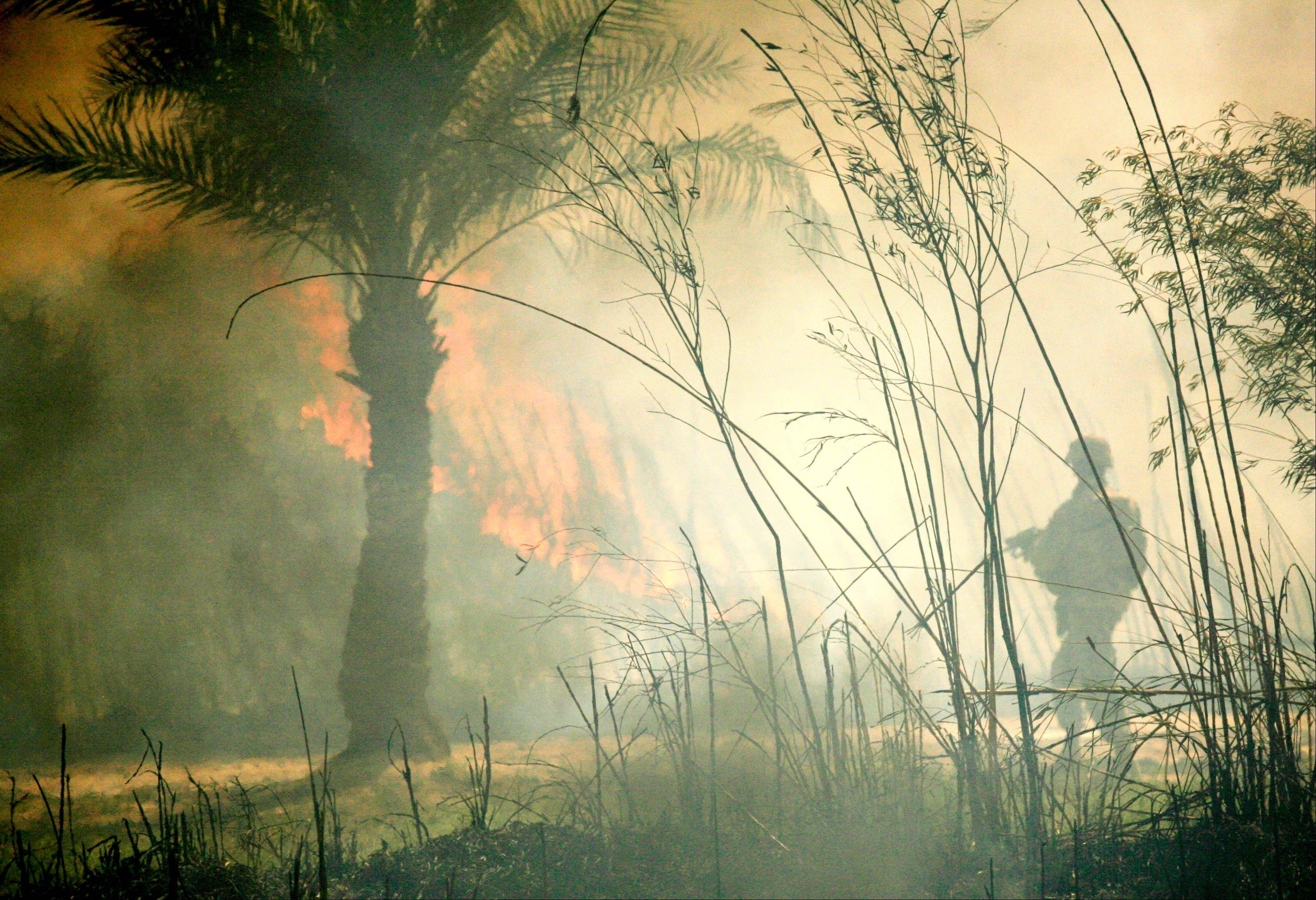A soldier from the Alpha Company, 4th Battalion, 31st Infantry Regiment walks past burning reeds razed to prevent insurgents from seeking cover in Quarghuli village near Youssifiyah, 12 miles south of Baghdad, Iraq, Saturday, May 26, 2007, two weeks after a May 12 ambush left four U.S. soldiers and an Iraqi soldier dead and three missing.