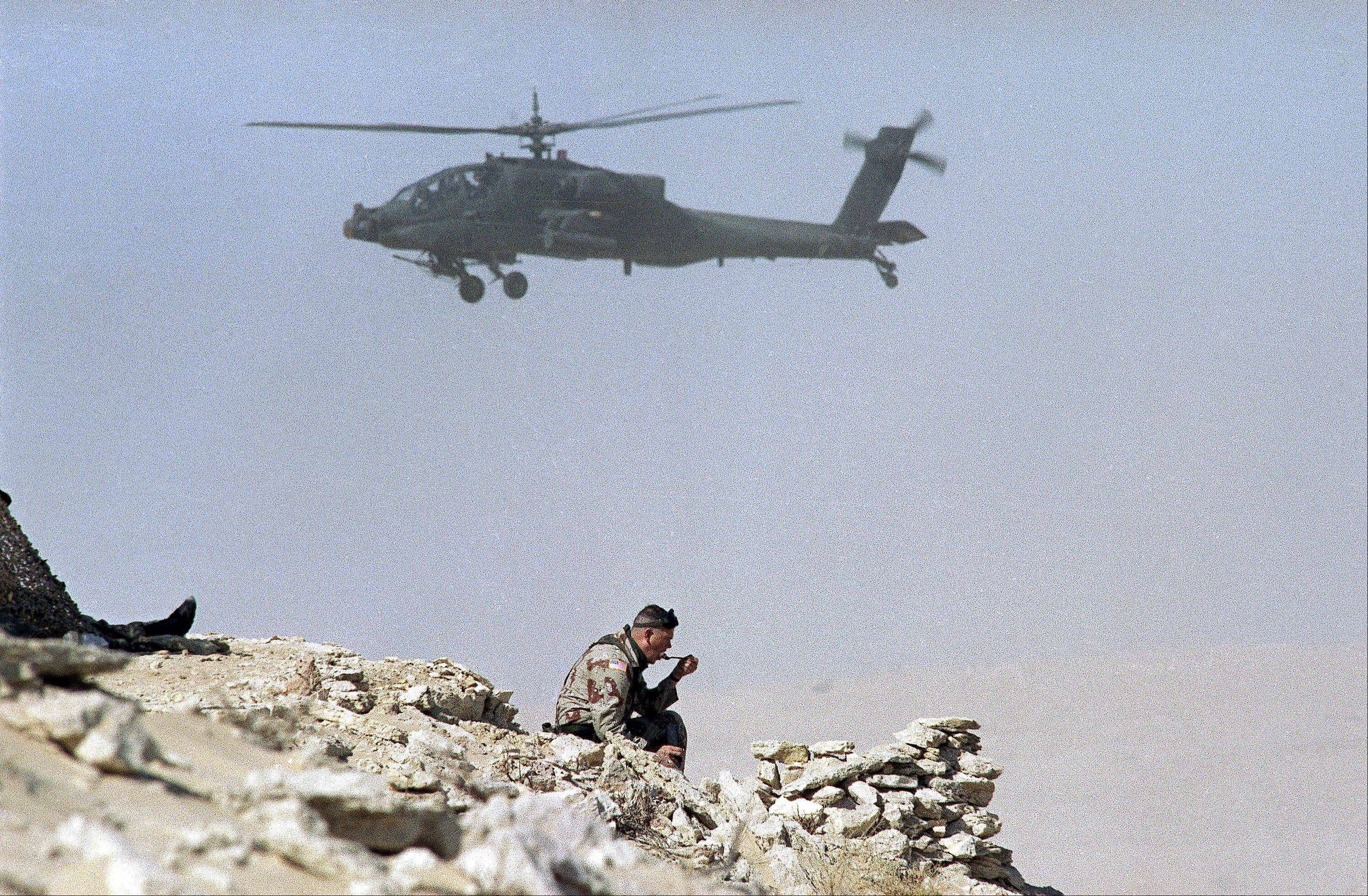 U.S. Army 2nd Lt. Tony Ferguson, of Bahama, NC, eats a field ration in the Saudi desert as an AH-64 Apache attack helicopter hovers nearby, Saturday, Nov. 10, 1990 in Saudi Arabia.