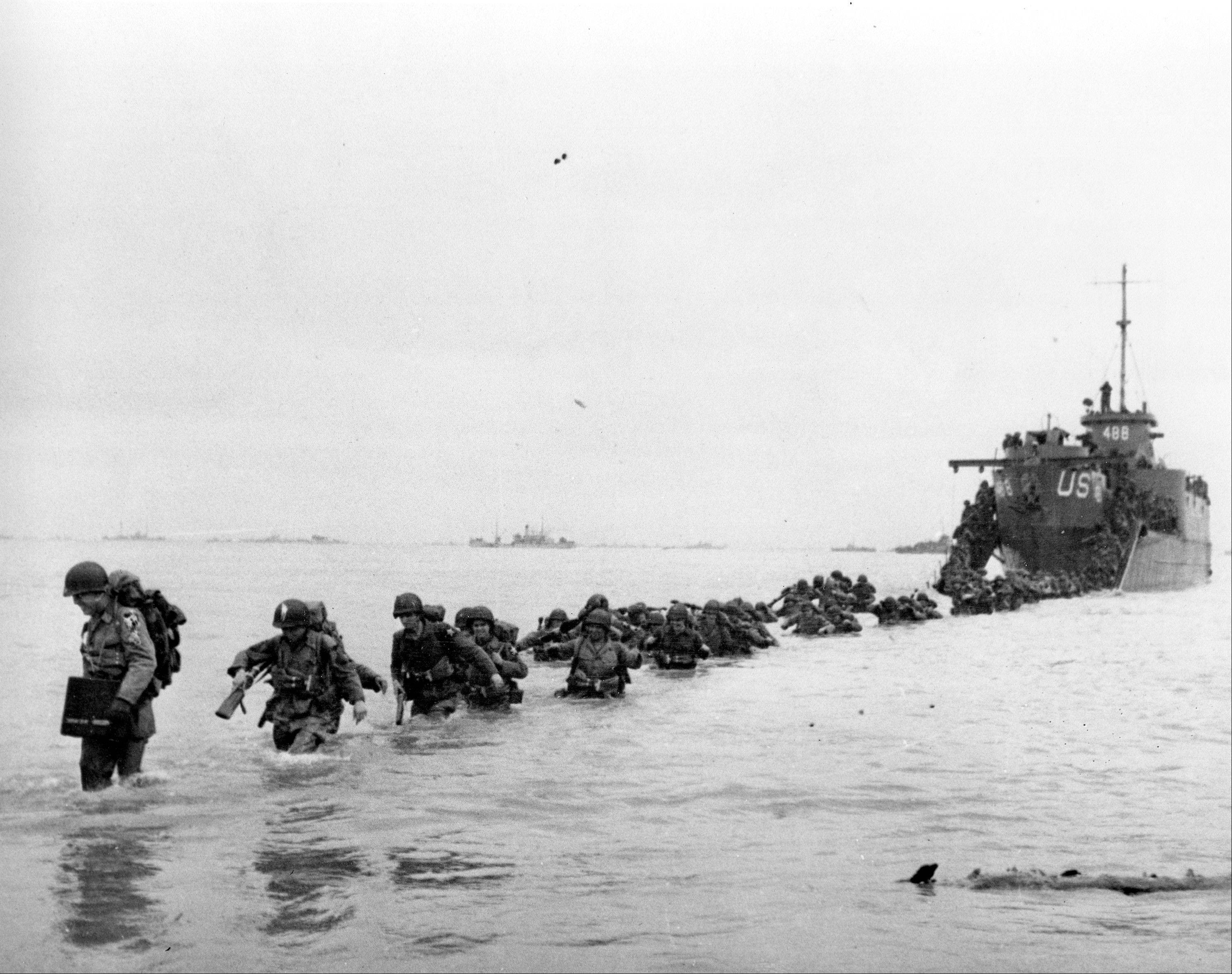 U.S. reinforcements wade through the surf from a landing craft in the days following D-Day and the Allied invasion of Nazi-occupied France at Normandy in June 1944 during World War II.