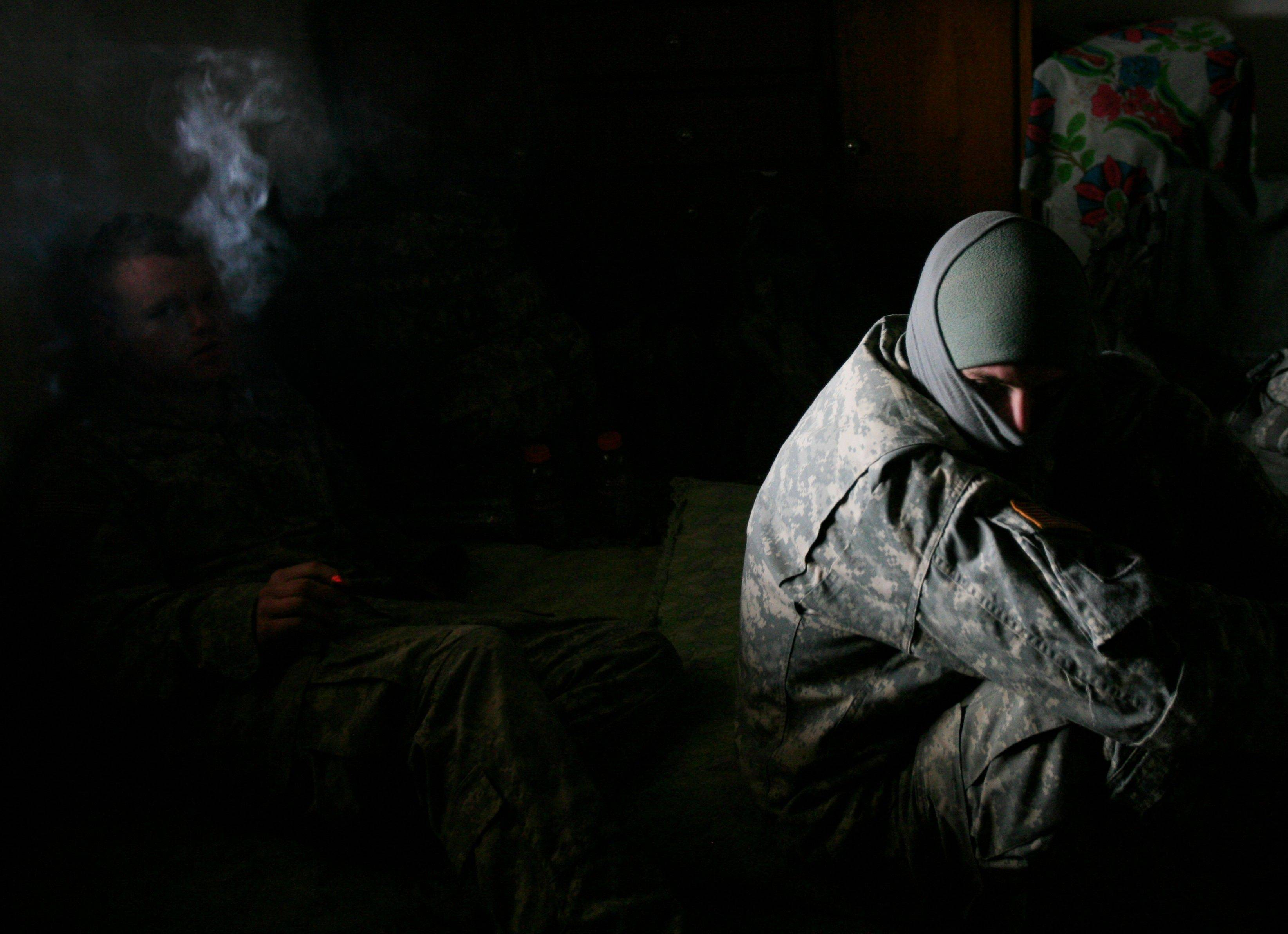 U.S. Army Pfc. Matthew Fazio, right, 25, bundles up against the bitter cold as soldiers from Alpha Company, 1st Battalion, 30th Infantry Regiment occupy a house in Arab Jabour during Operation Coliseum south of Baghdad, Iraq on Wednesday, Jan. 23, 2008.