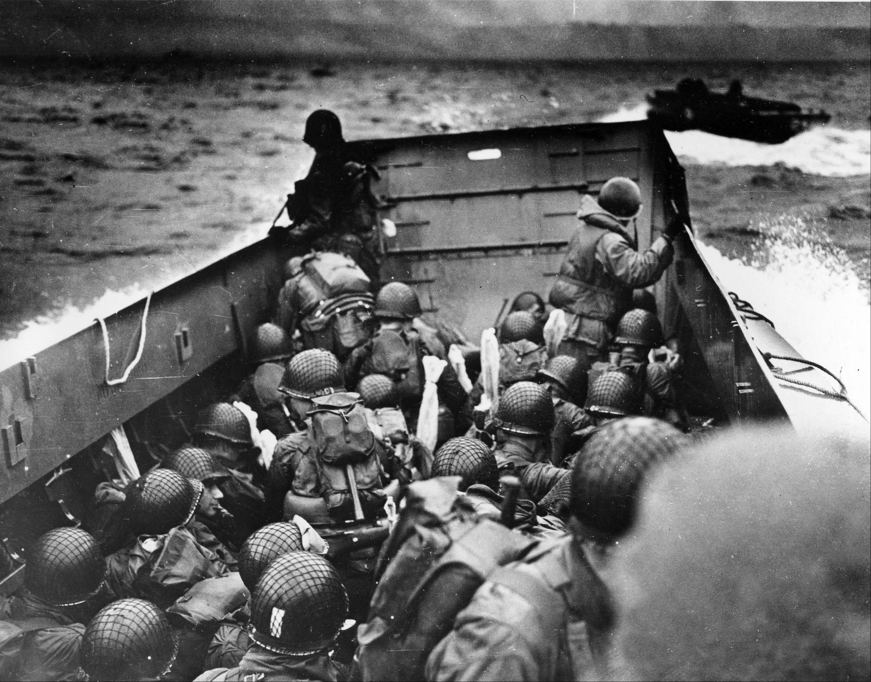 In this photo provided by the U.S. Coast Guard, a U.S. Coast Guard landing barge, tightly packed with helmeted soldiers, approaches the shore at Normandy, France, during initial Allied landing operations, on June 6, 1944.