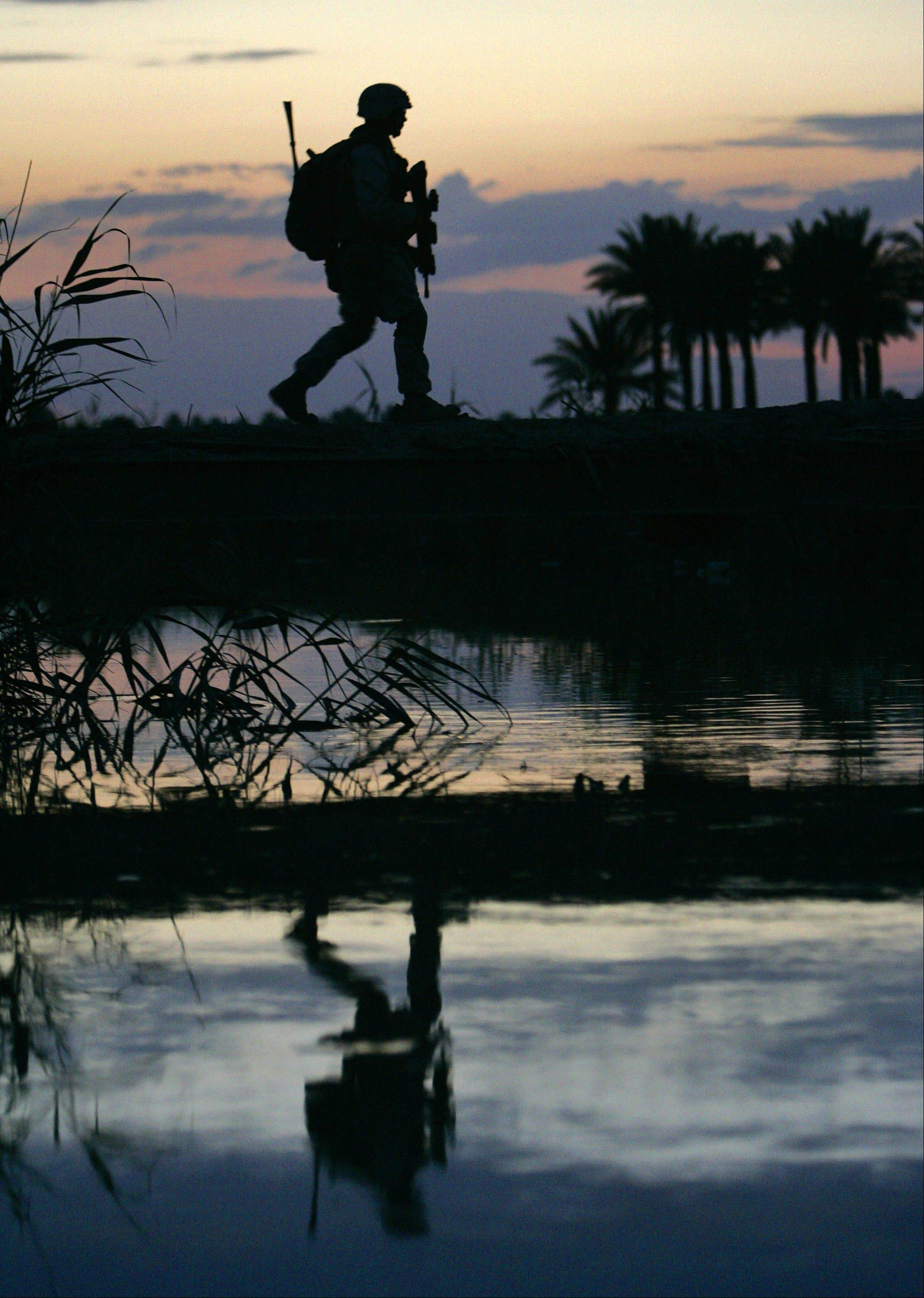 A U.S. Marine crosses a footbridge while patrolling in Karmah, 50 miles west of Baghdad, Iraq, Wednesday, April 26, 2006.