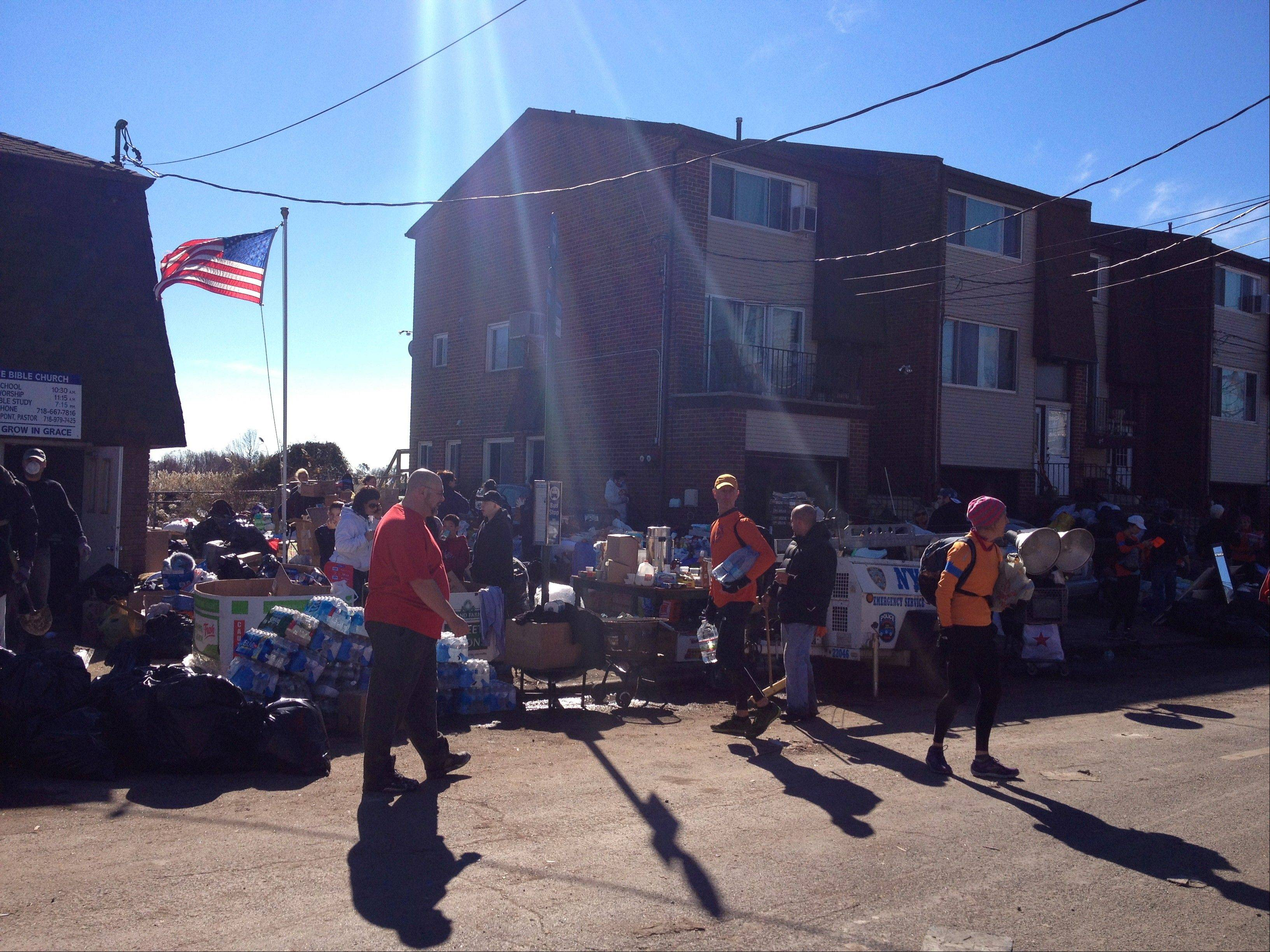 Volunteers help hand out food and water to Staten Island residents Nov. 4 during relief efforts in the wake of Hurricane Sandy. The group of largely would-be marathoners was organized by NYC Marathon of Relief Efforts once the race was canceled and runners were left with an open day.