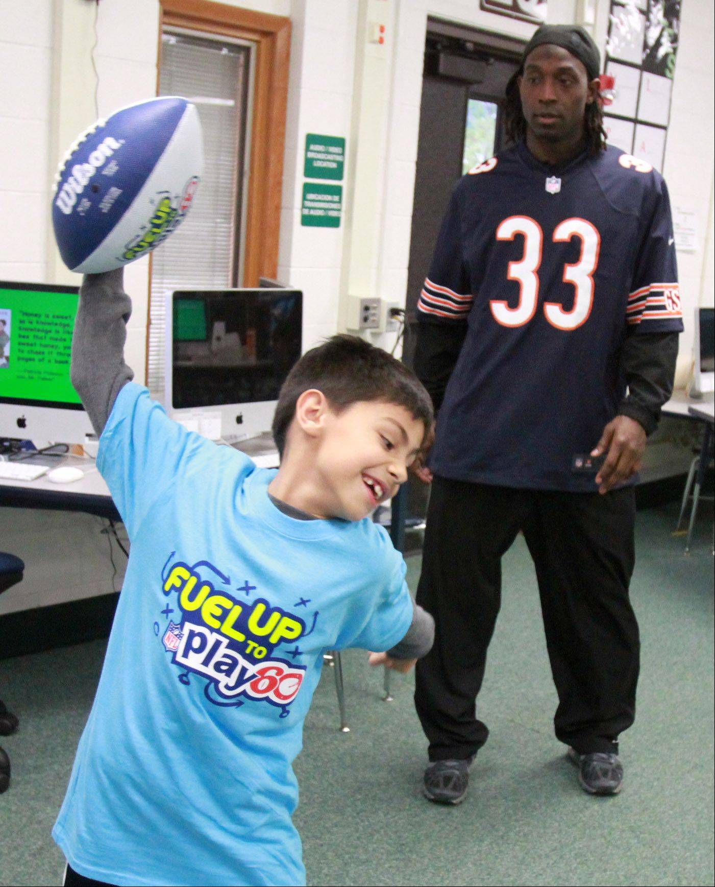 "Third-grader Denis Webster spikes a football after getting a short pass from Chicago Bears' cornerback Charles ""Peanut"" Tillman who was visiting students at Ridge Family Center for Learning in Elk Grove Village on Wednesday, November 6. Tillman, quarterback Jason Campbell, and center/guard Roberto Garza were at the school for the filming of a national TV feature for NFL Play 60 and Kinect for Xbox 360"