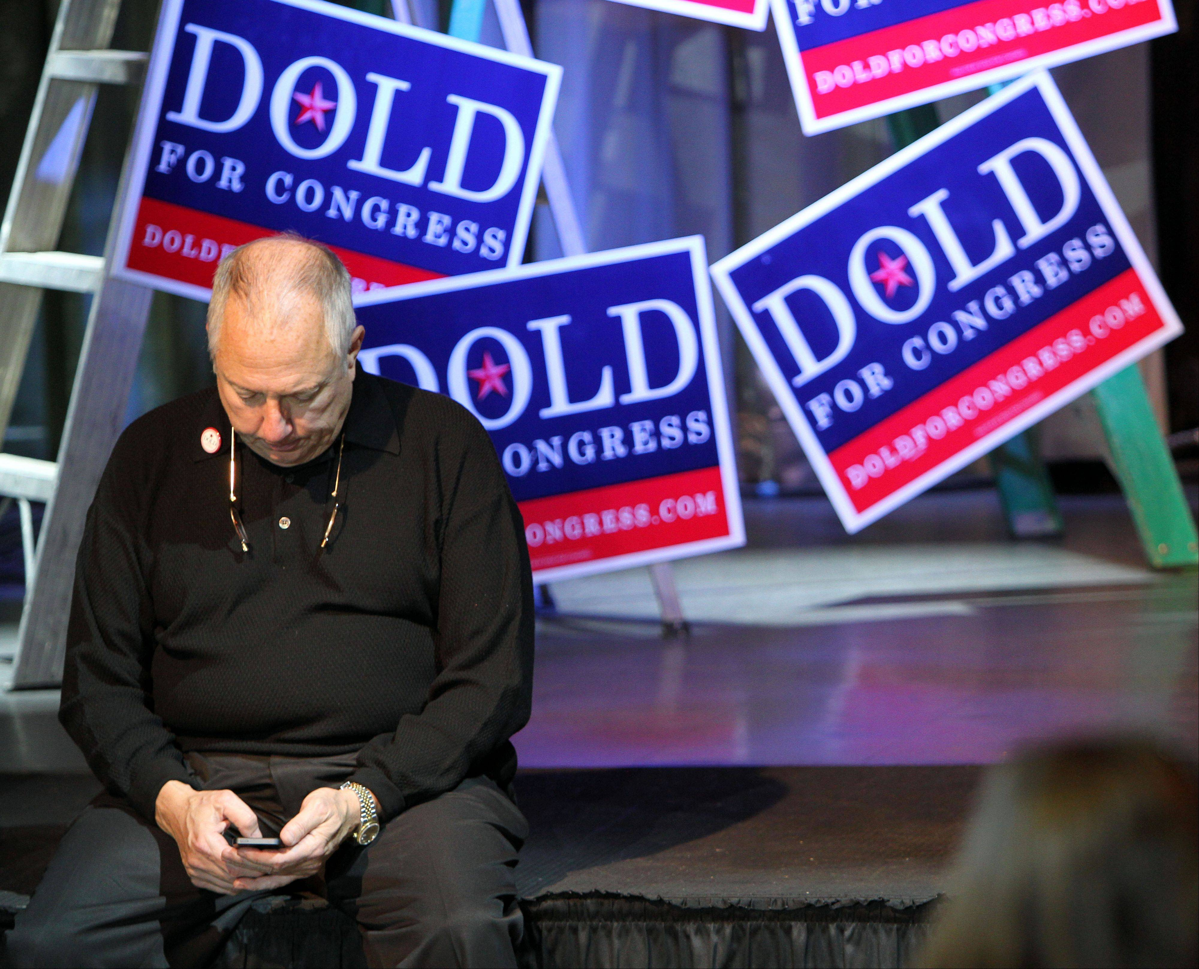 Dold supporter Richard Stein of Glenview watches the election returns on his phone at Dold headquarters in Lincolnshire at Viper Alley Tuesday night.