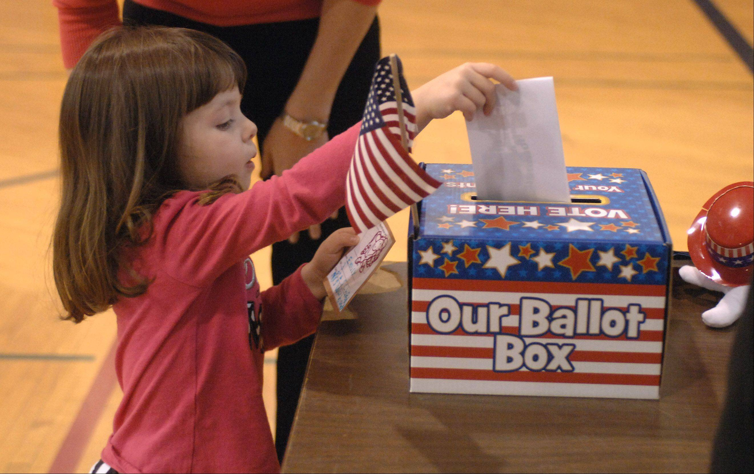Preschool student Emily Horbus, 3, places her ballot in the box after voting for a president in a mock election Tuesday at St. Matthew Lutheran School in Hawthorn Woods. Students have been learning about the voting process and the candidates and around 115 students and teachers voted.