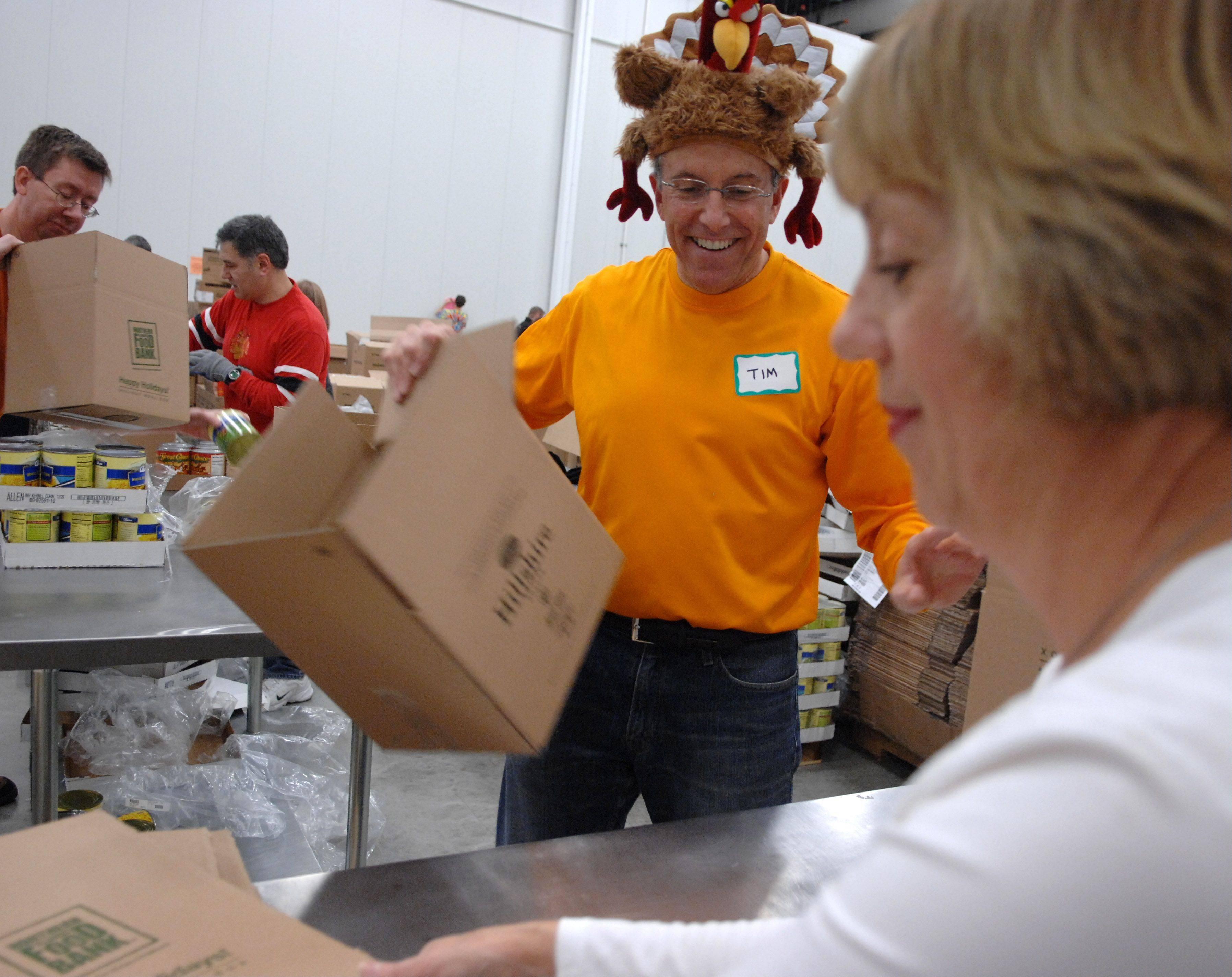 Tim and Donna O'Connor of Wheeling make boxes that are to be loaded with holiday meals as more than 100 employees from Jewel-Osco volunteer at the Northern Illinois Food Bank in Geneva Saturday. It�s the kickoff to a six-week program during which the food bank will pack more than 30,000 holiday meals for the less fortunate.