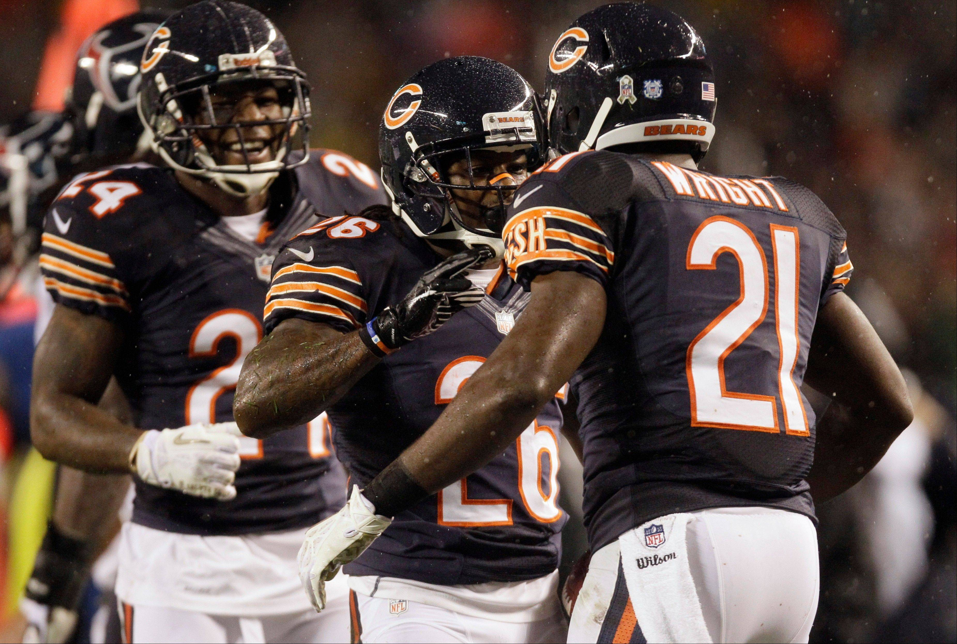 Bears cornerback Tim Jennings (26) celebrates his interception against the Houston Texans with teammates Kelvin Hayden (24) and Major Wright (21) in the first half an NFL football game in Chicago, Sunday, Nov. 11, 2012.