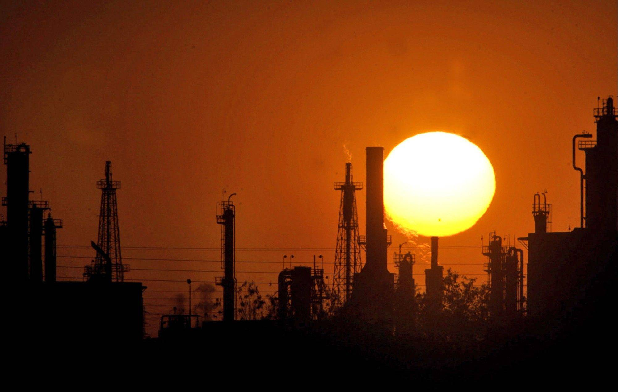 The sun sets behind an oil refinery in Bakersfield, Calif. The prospect of the United States becoming the world's leading oil producer in the next couple decades has served as wakeup call for Canada, which is currently America's leading oil supplier.