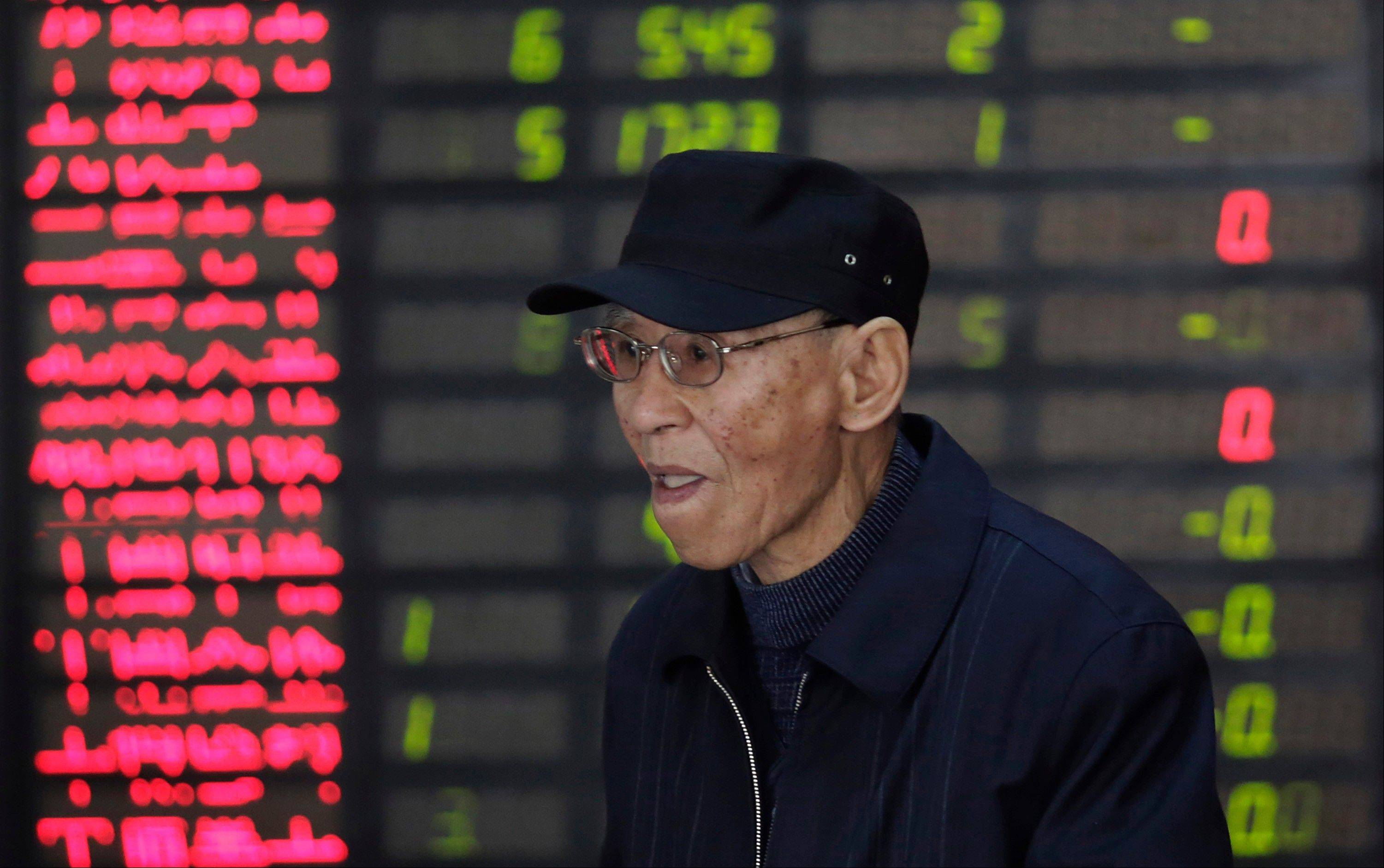 An investor looks at the stock price monitor at a private securities company in Shanghai, China Tuesday