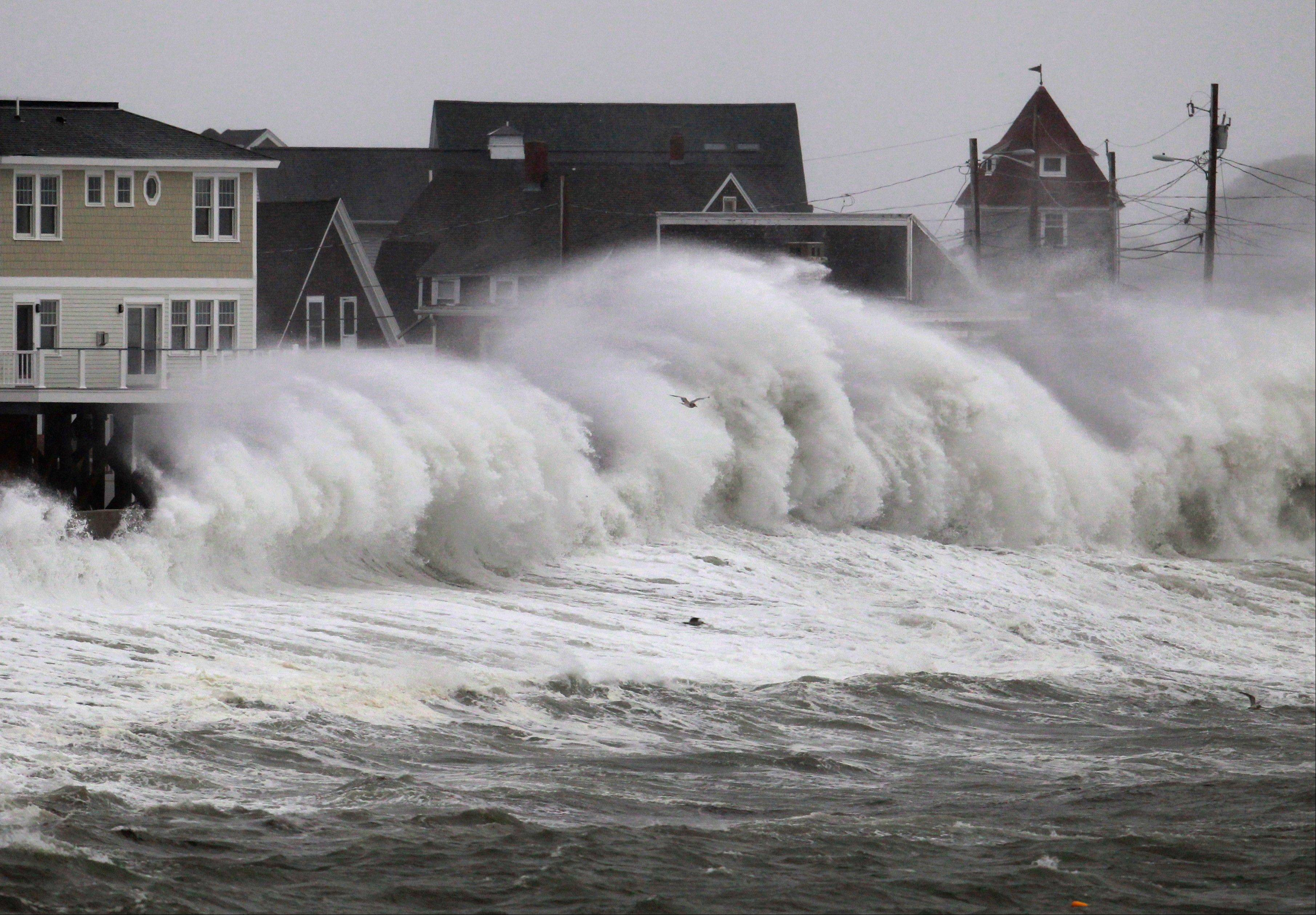 Waves crash into a seawall and buildings along the coast in Hull, Mass., last Wednesday. Superstorm Sandy has added power to those who maintain global climate change is increasing the frequency of destructive storms.
