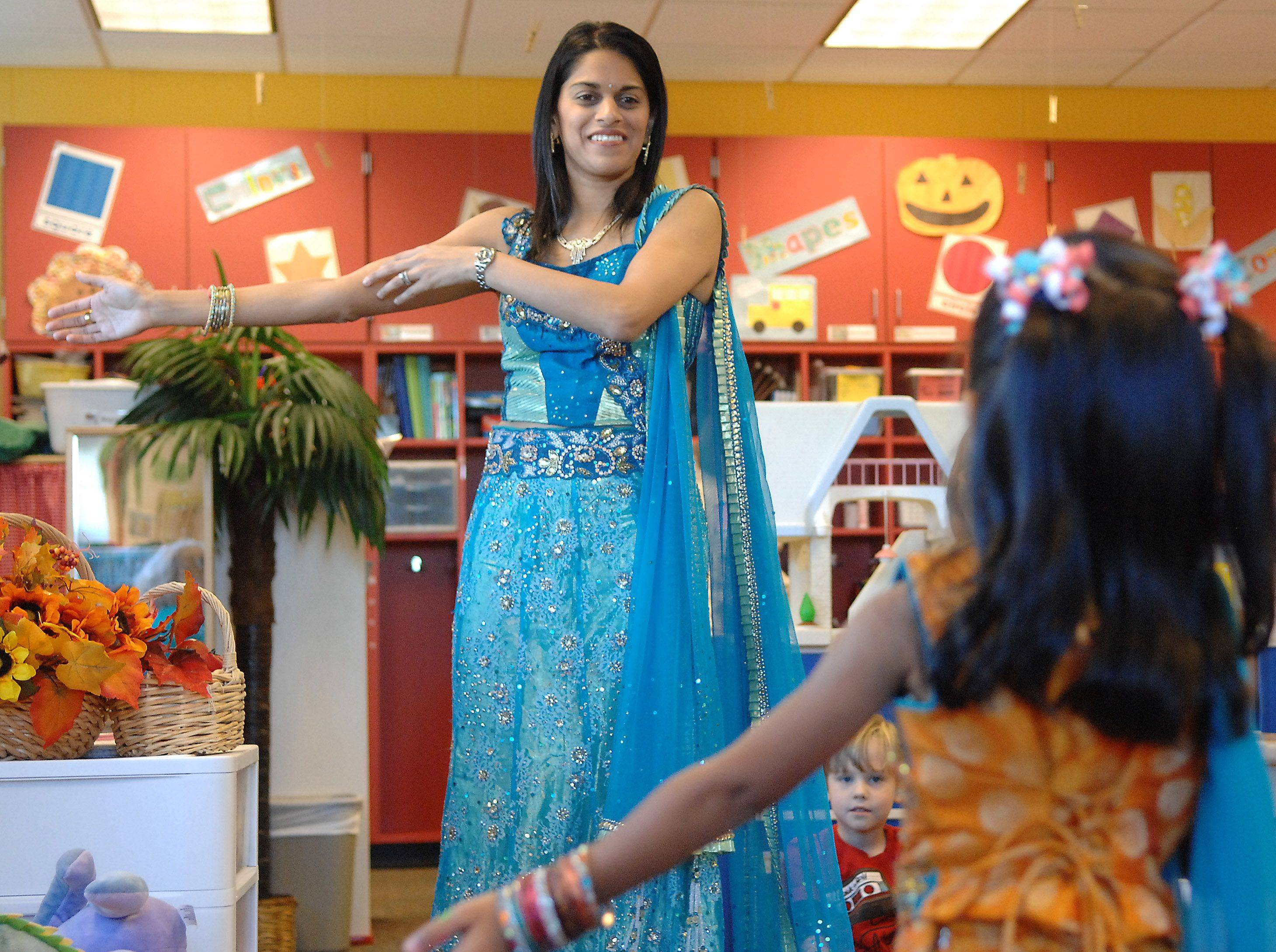 Liza Jain of Geneva helps lead her daughter Anishka, 3, in a modern Indian Bollywood-style dance while teaching Anishka's preschool classmates about the Indian festival of Diwali Tuesday at Friendship Station in Geneva.