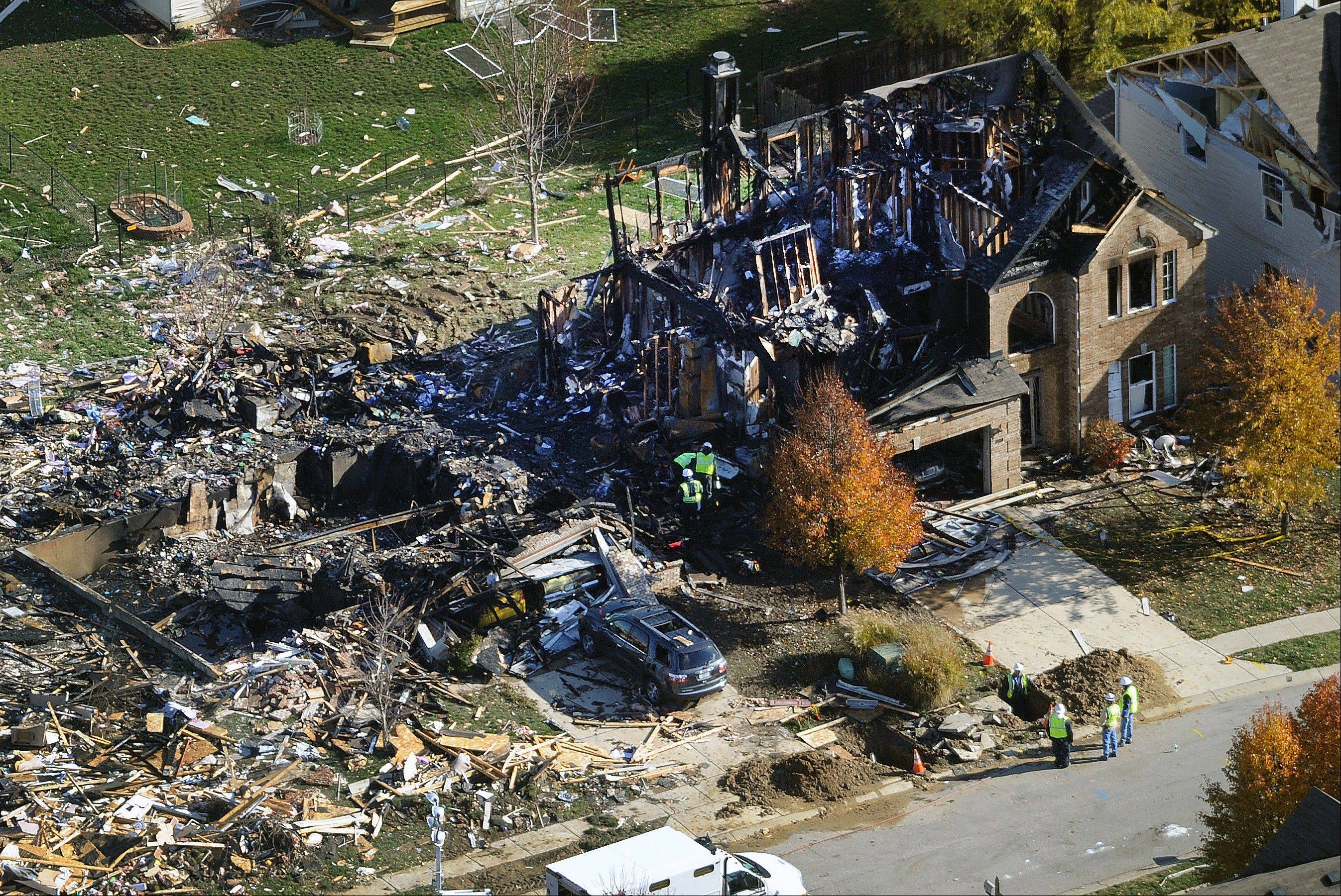 Citizens Energy workers continue their investigation Monday, Nov. 12, 2012, at the site of an explosion at a house in Indianapolis. The search for what caused a massive, deadly explosion that rocked an Indianapolis neighborhood turned to natural gas Monday, with officials checking gas lines and a homeowner saying a problem furnace could be to blame.
