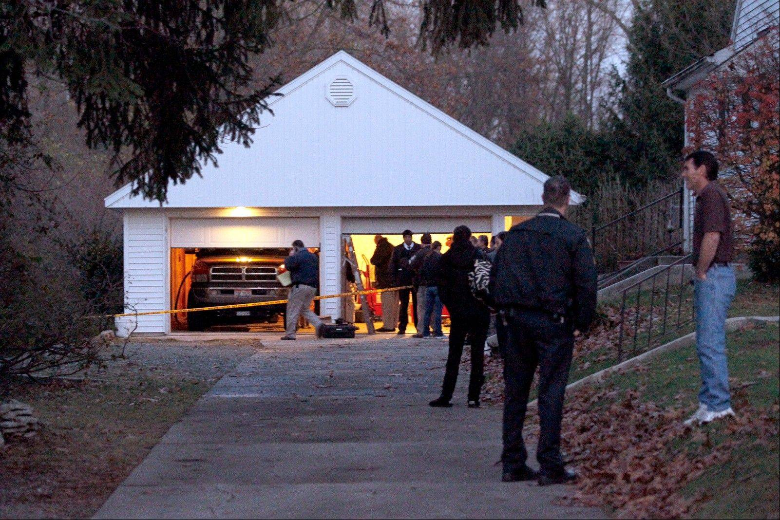 Authorities respond to a report of carbon monoxide poisoning in Toledo, Ohio, Monday. The bodies of three children and two adults were found inside the garage.