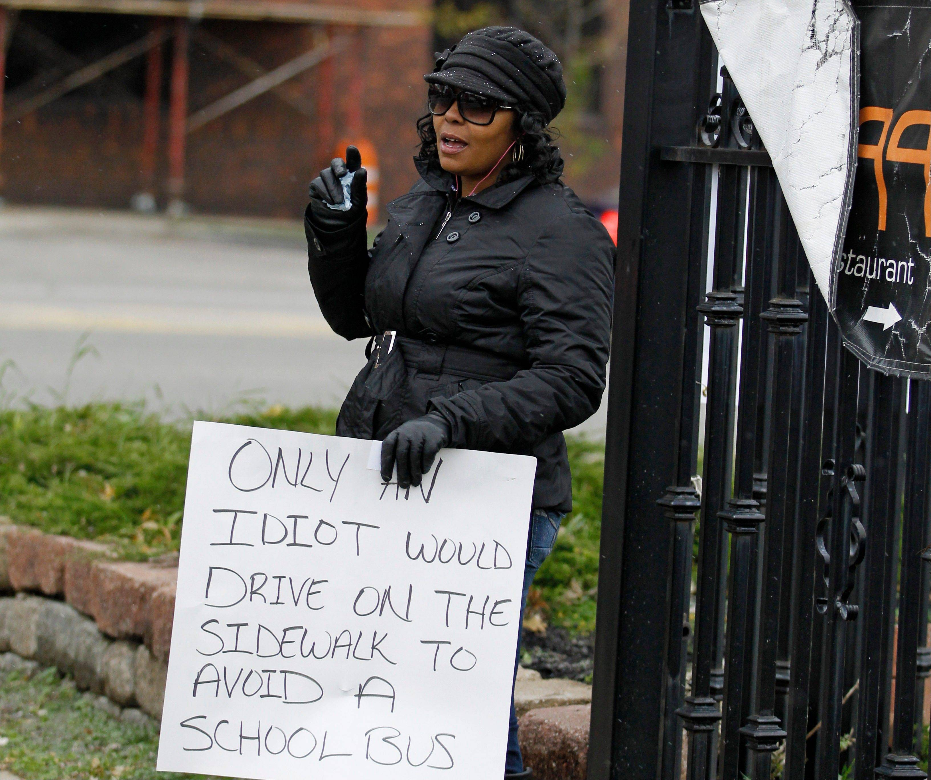 Shena Hardin holds up a sign to serve a highly public sentence Tuesday, Nov. 13, 2012, in Cleveland, for driving on a sidewalk to avoid a Cleveland school bus that was unloading children. A Cleveland Municipal Court judge ordered 32-year-old Hardin to serve the highly public sentence for one hour Tuesday and Wednesday.
