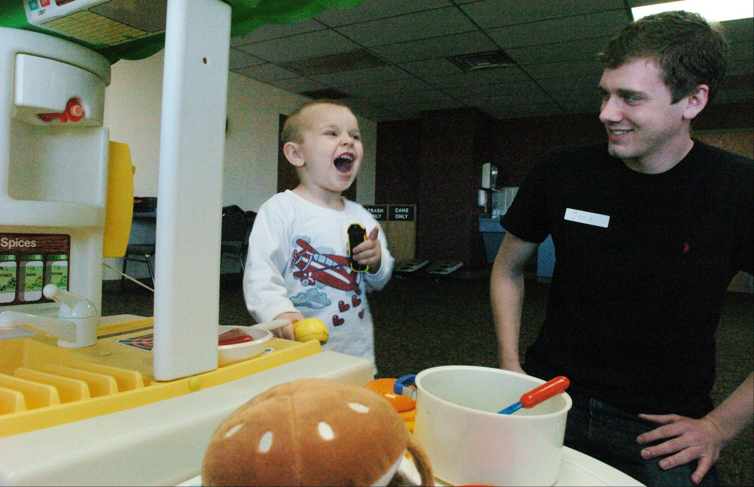 Austin Payne, 2, of Wheaton, spends time with Jack Gende during a recent visit to the NEDSRA headquarters in Addison as part of the Take a Break in the Afternoon program.