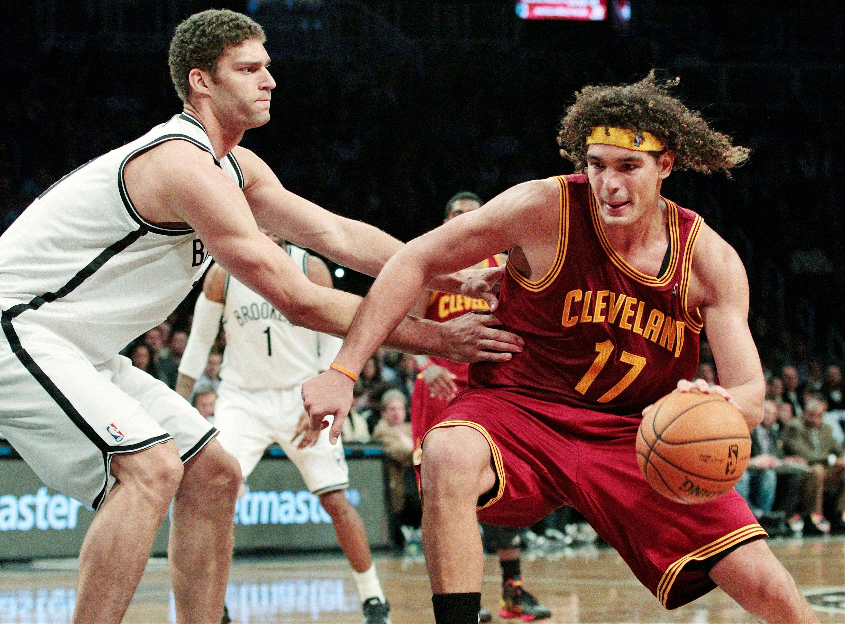 The Brooklyn Nets' Brook Lopez defends the Cleveland Cavaliers' Anderson Varejao Tuesday during the second half in New York. The Nets won 114-101.