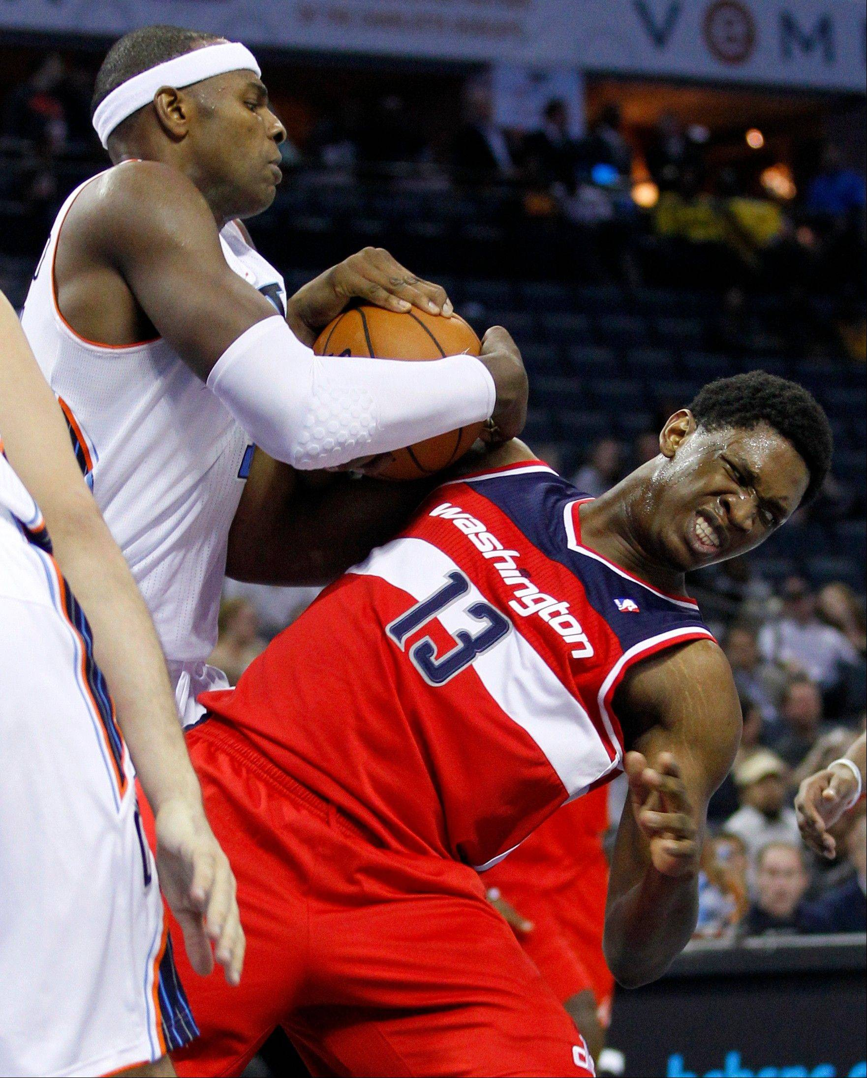The Charlotte Bobcats' Brendan Haywood, left, wrestles the ball from the Washington Wizards' Kevin Seraphin, right, Tuesday during the second half in Charlotte, N.C. Charlotte won 92-76.