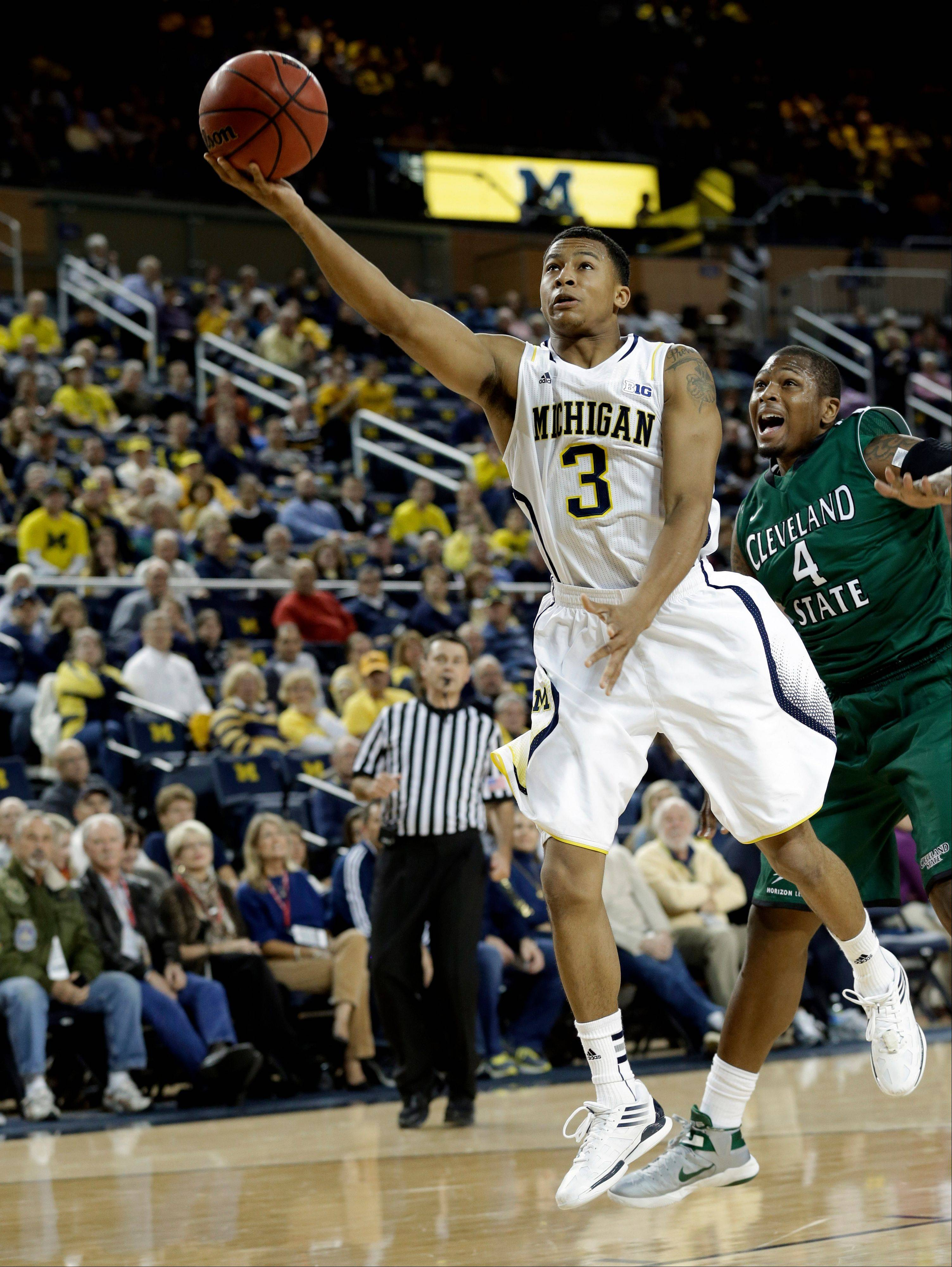 Michigan guard Trey Burke drives past Cleveland State center Devon Long Tuesday during the first half in the second-round of the NIT Season Tip-Off tournament at Crisler Arena in Ann Arbor, Mich.