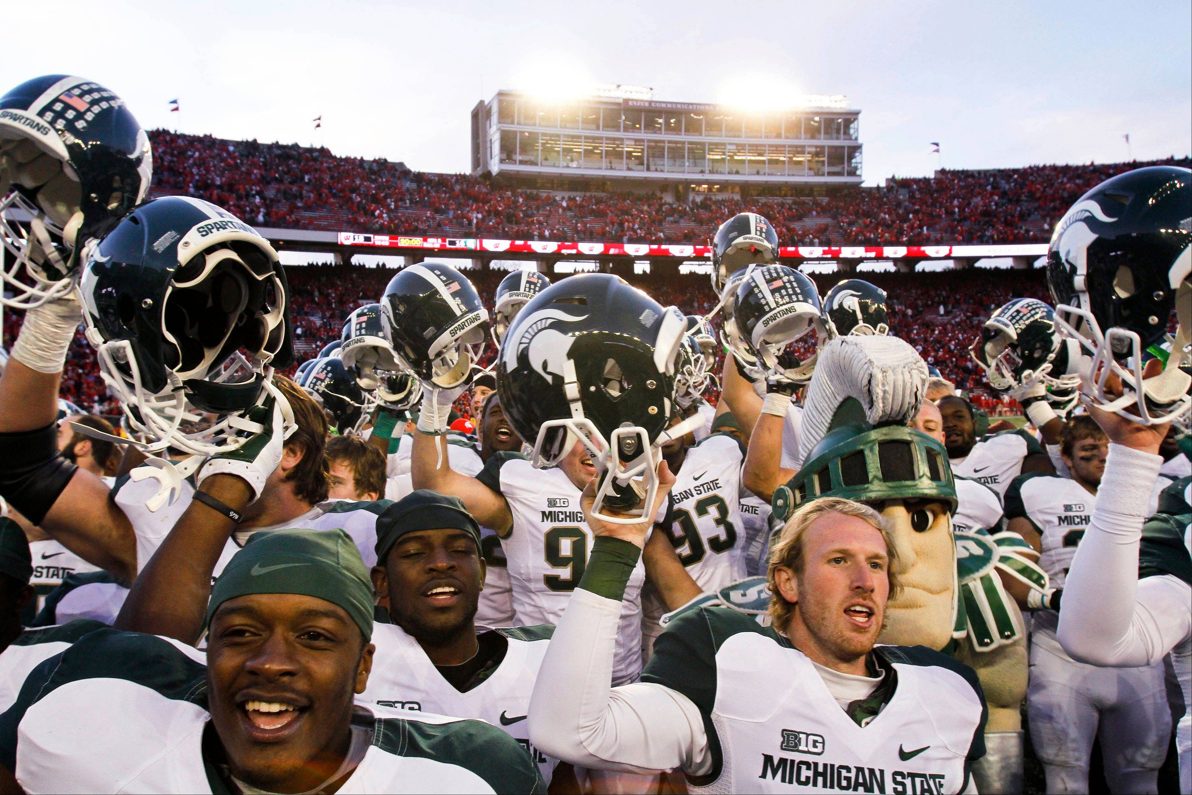 Michigan State players celebrate after defeating Wisconsin 16-13 in overtime in Madison, Wis.