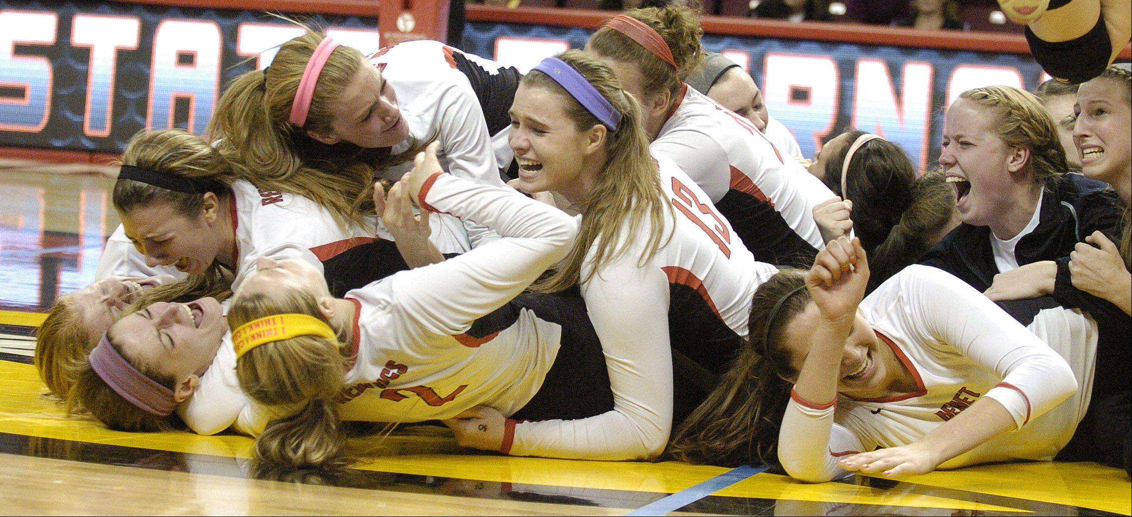 Benet players hit the floor in celebration after winning the Class 4A girls volleyball championship game Saturday.