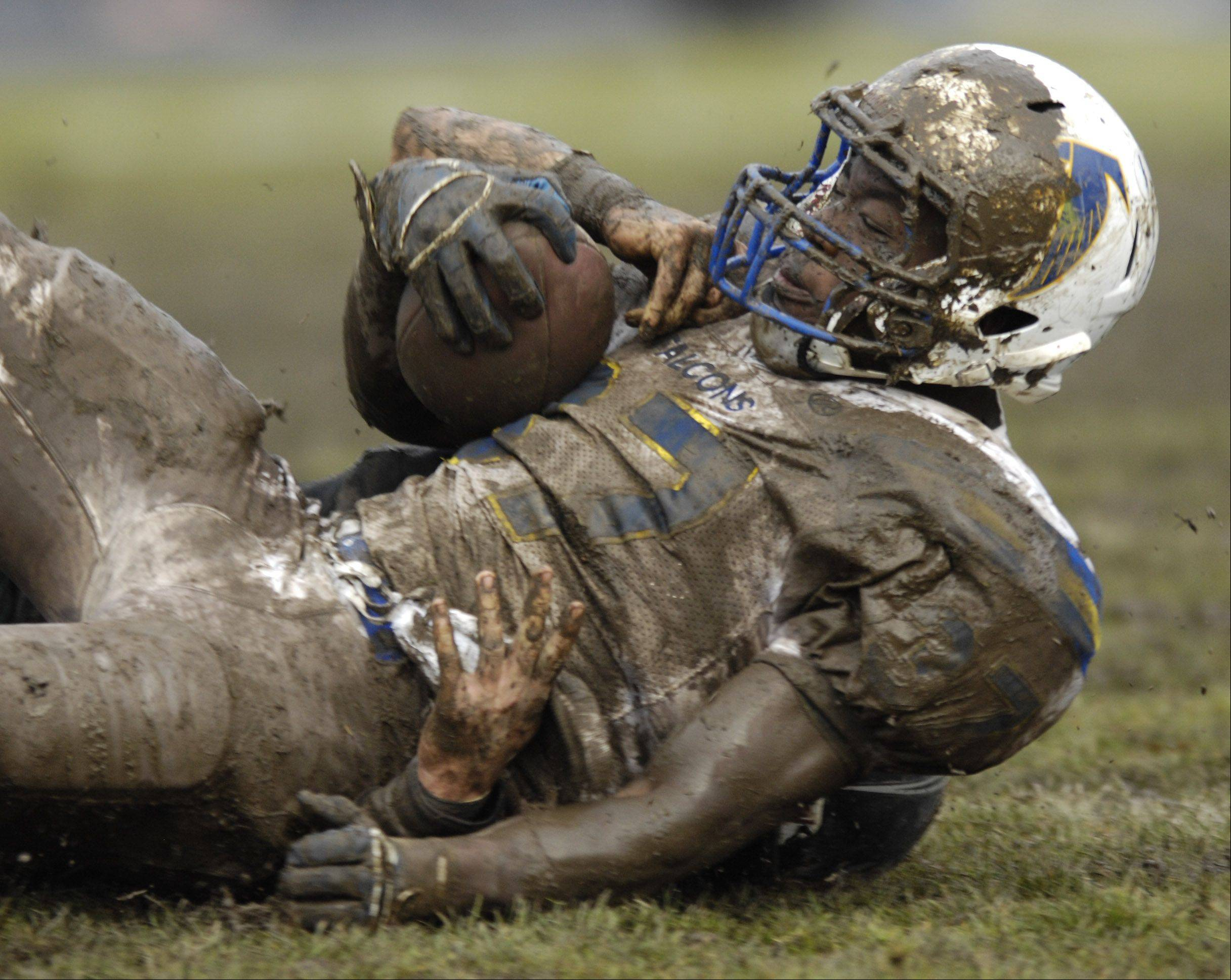 Wheaton North running back Patrick Sharp is covered with mud after being tackled during Saturday's game against Glenbard West.