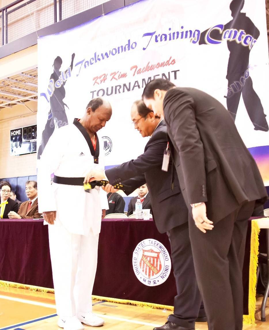 The Honorable Secretary of State Jesse White Receives an Honorary 4th Dan Black Belt from Grandmaster Ki Hong Kim, founder of KH Kim Taekwondo & the World Taekwondo Training Center, at the 10th KH Kim Taekwondo Tournament, November 4, 2012, held at the Glen Ellyn Ackerman Sports & Fitness Center.