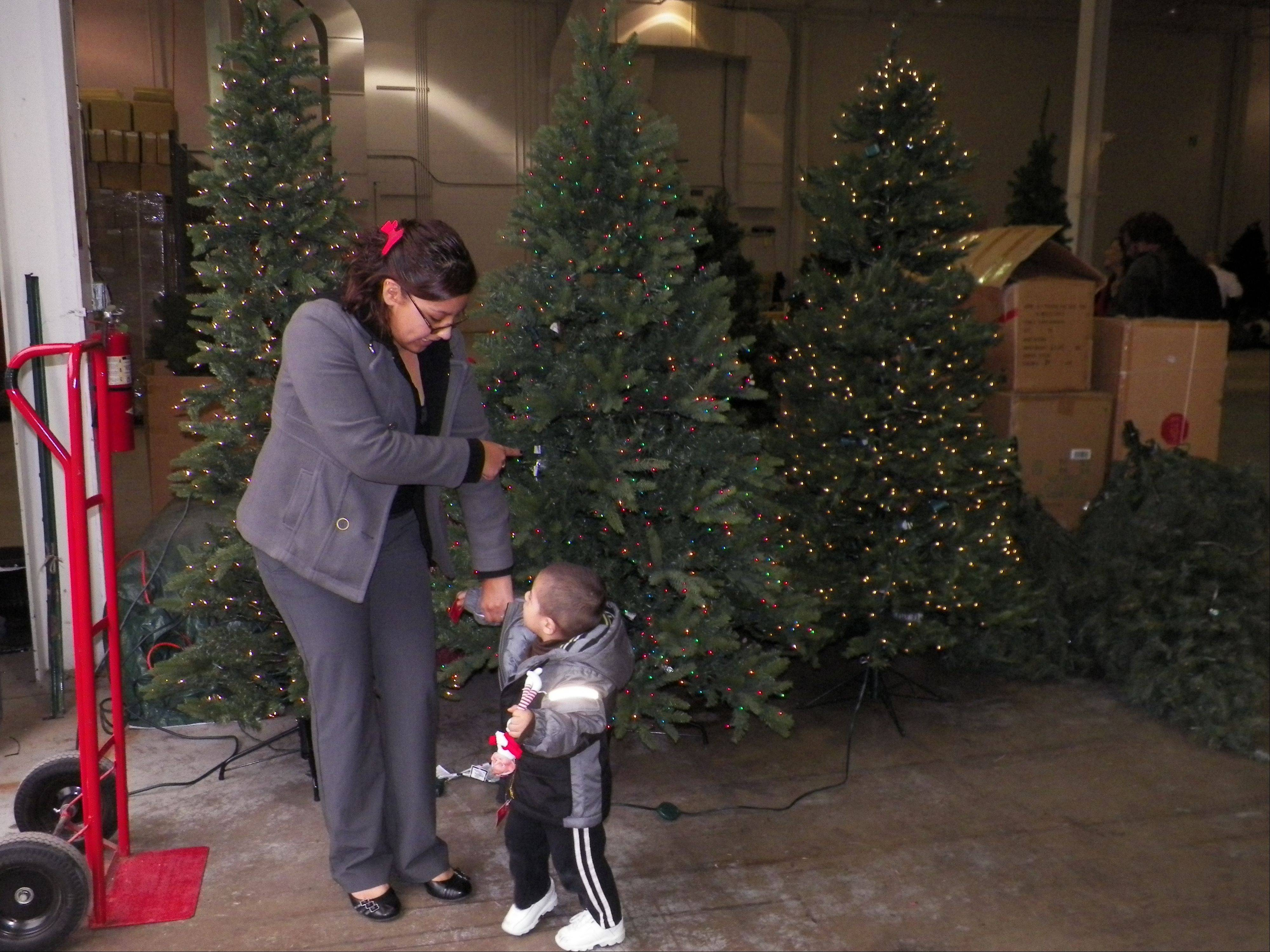 Marisa Soto, a single mother who lives in Waukegan, and her son Jayden, 1�, pick out an artificial Christmas tree at Treetime Christmas Creations in Lake Barrington in a program with Salvation Army.