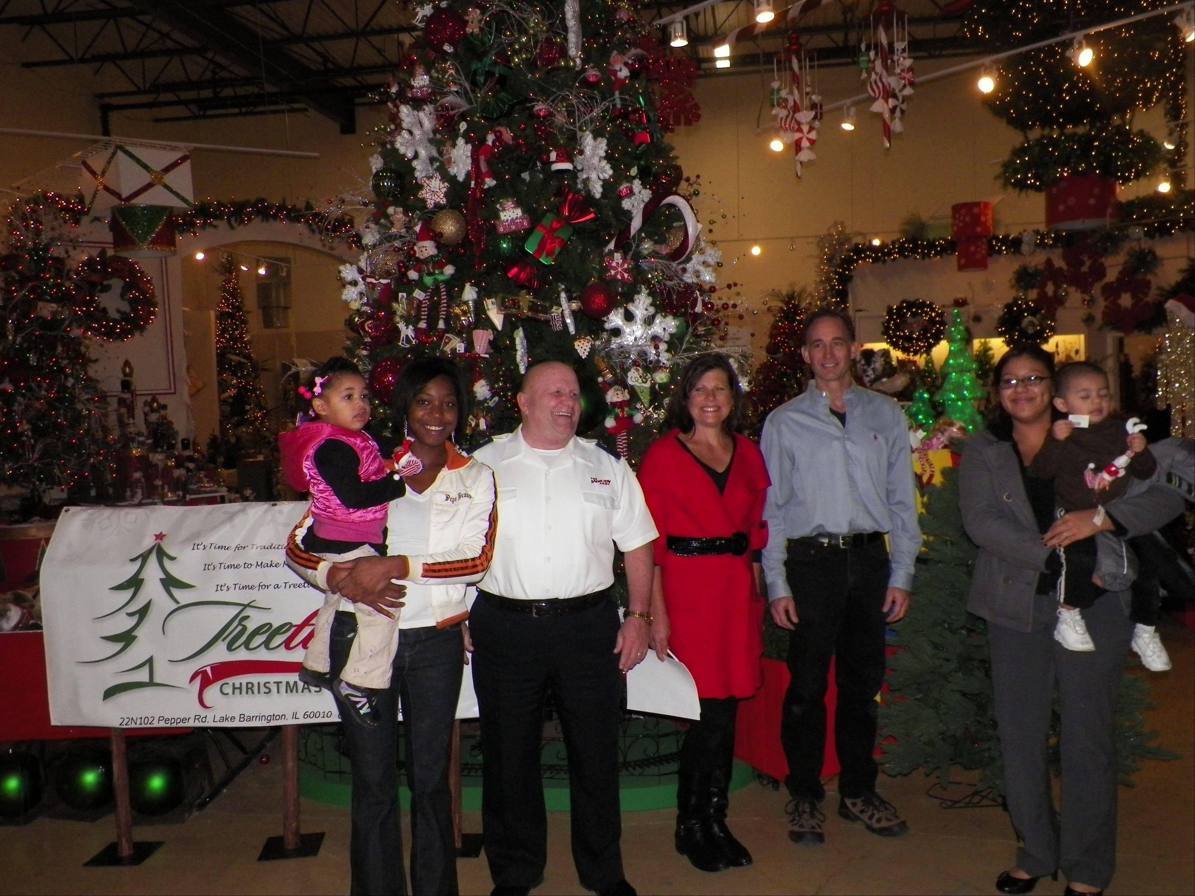 From left, Versatility Johnson and her daughter Zamya, 2, of North Chicago pose with Salvation Army Envoy Dennis Earnhart, Laurie and Joe Kane of Treetime Christmas Creations, and Marisa Soto and son Jayden, 1�, of Waukegan. The single moms were at the Lake Barrington business to pick out Christmas trees.