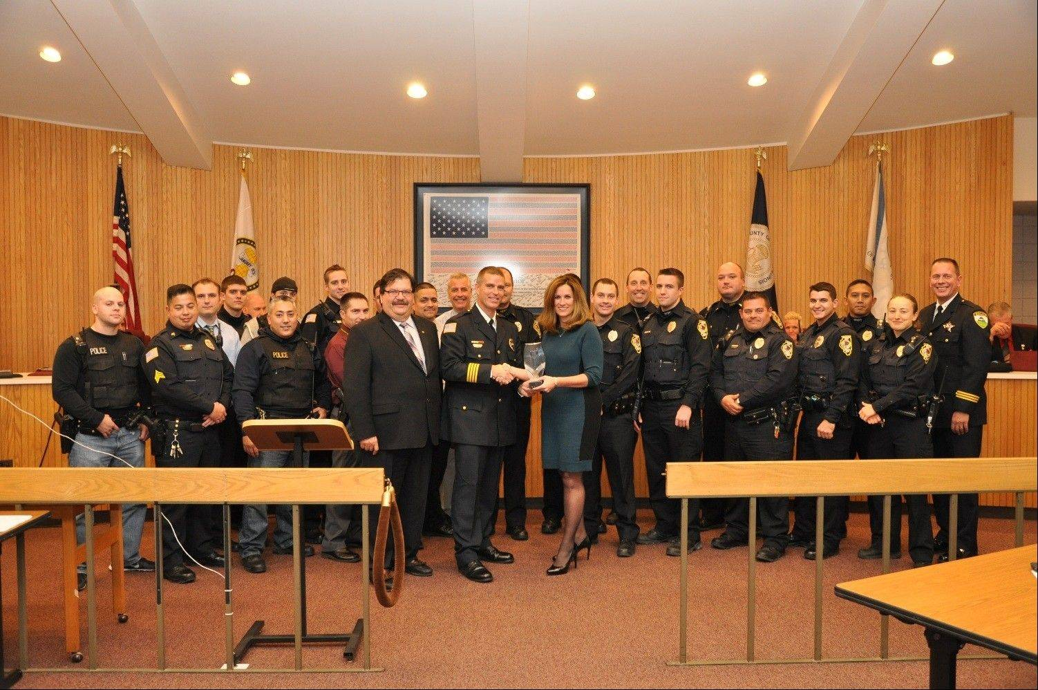 Pictured at the village board meeting are: Village President Rod Craig; Police Chief David Webb; Kim Majerus, vice president of Cisco; and to the far right, Itasca Police Chief and IACP Community Policing Committee representative Scott Heher and several officers from the Hanover Park Police Department.