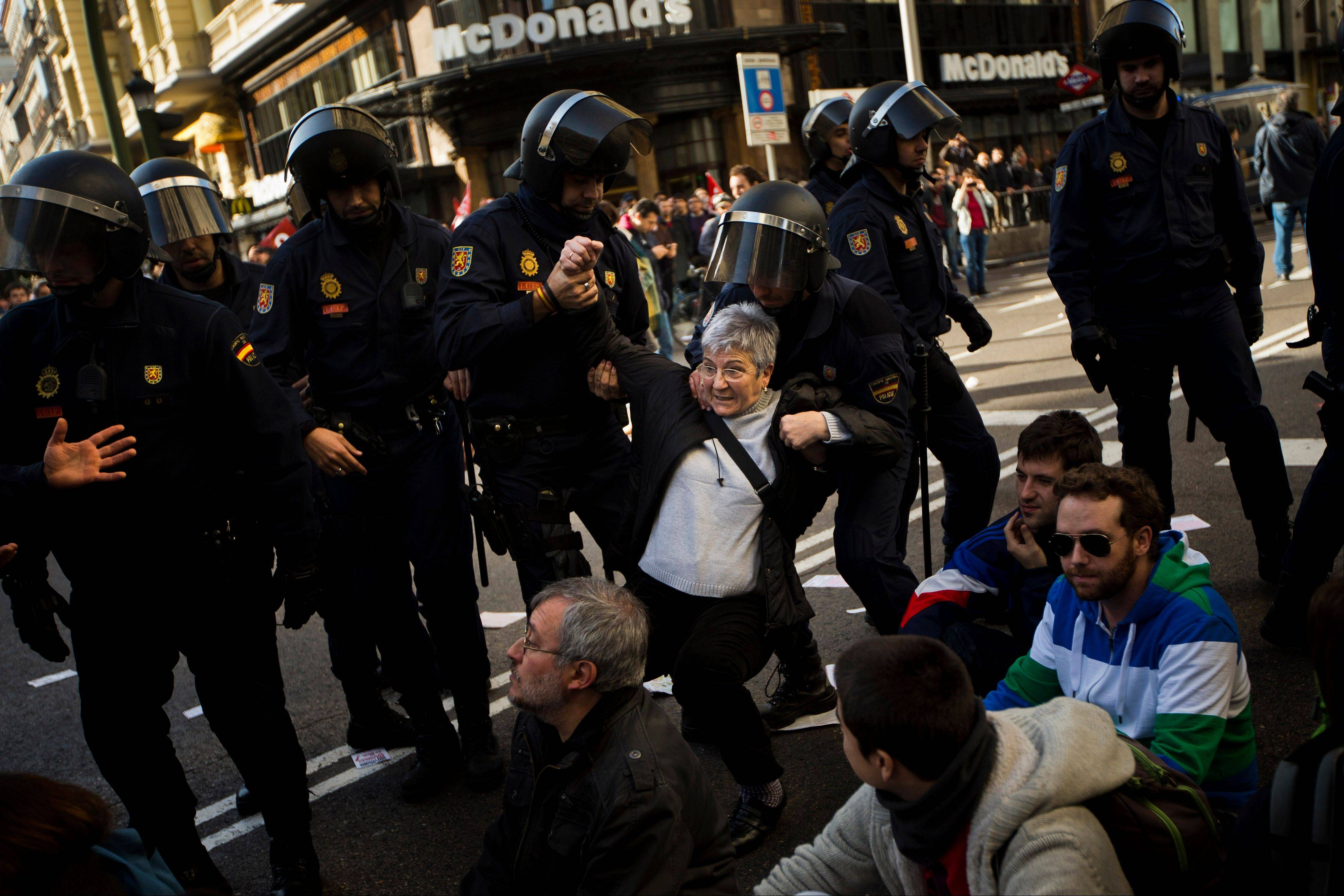 A protester is held by riot police during clashes in a general strike in Madrid, Spain, Wednesday, Nov. 14, 2012. Spain's General Workers' Union said the nationwide stoppage, the second this year, was being observed by nearly all workers in the automobile, energy, shipbuilding and constructions industries.