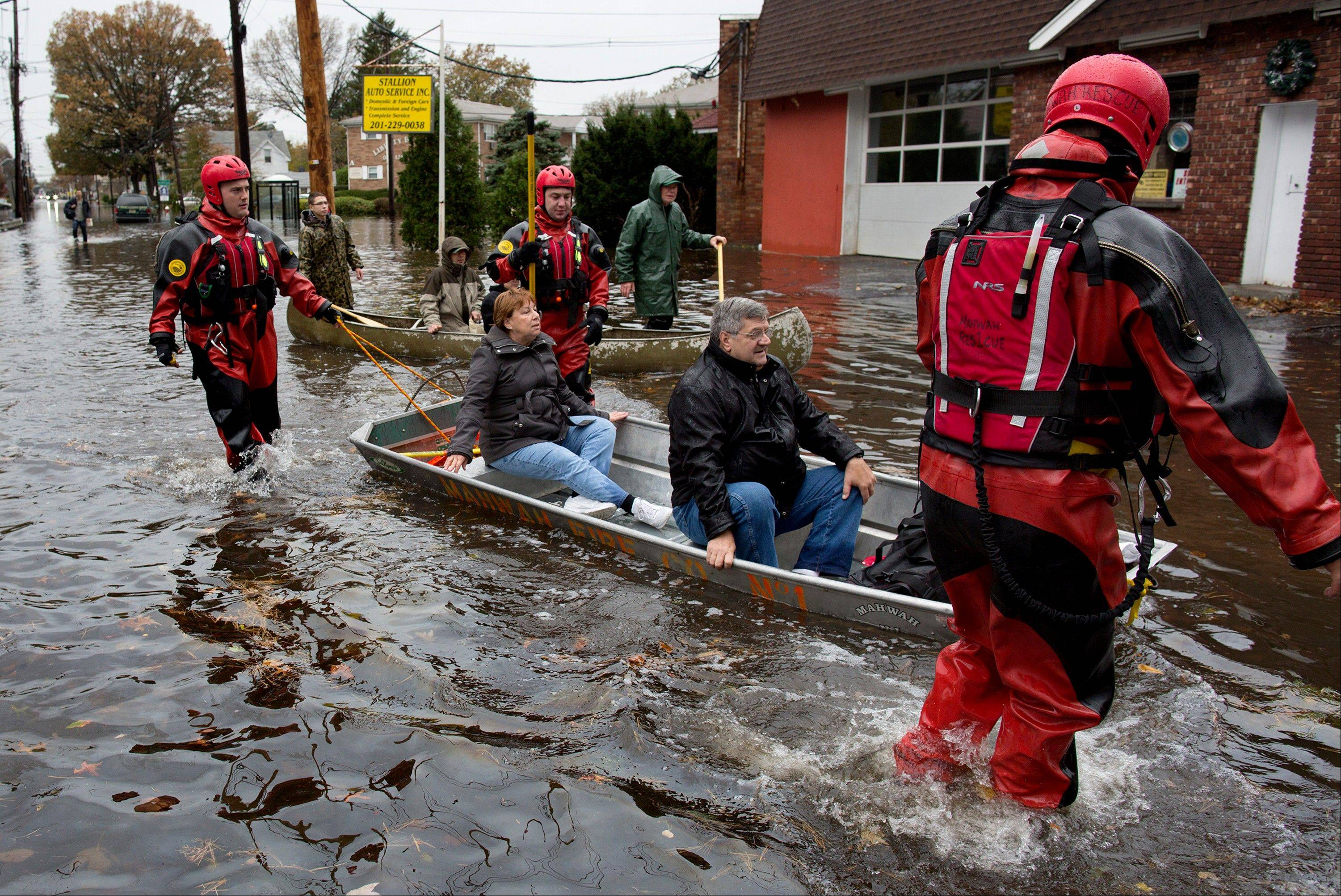 Rescuers bring people out by boat in the wake of superstorm Sandy in Little Ferry, N.J., on Oct. 30. Despite days of dire forecasts and explicit warnings, hundreds of thousands of people in New York and New Jersey ignored mandatory evacuation orders as Superstorm Sandy closed in.