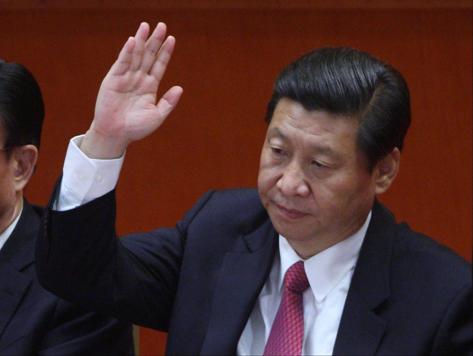 Xi Jinping, China's vice president, raises his hand during the closing session of the 18th National Congress of the Communist Party of China at the Great Hall of the People in Beijing, China, on Wednesday, Nov. 14, 2012. Xi and Vice Premier Li Keqiang were reappointed to the Chinese Communist Party's Central Committee, positioning them to take over the top two posts in the world's second-biggest economy.