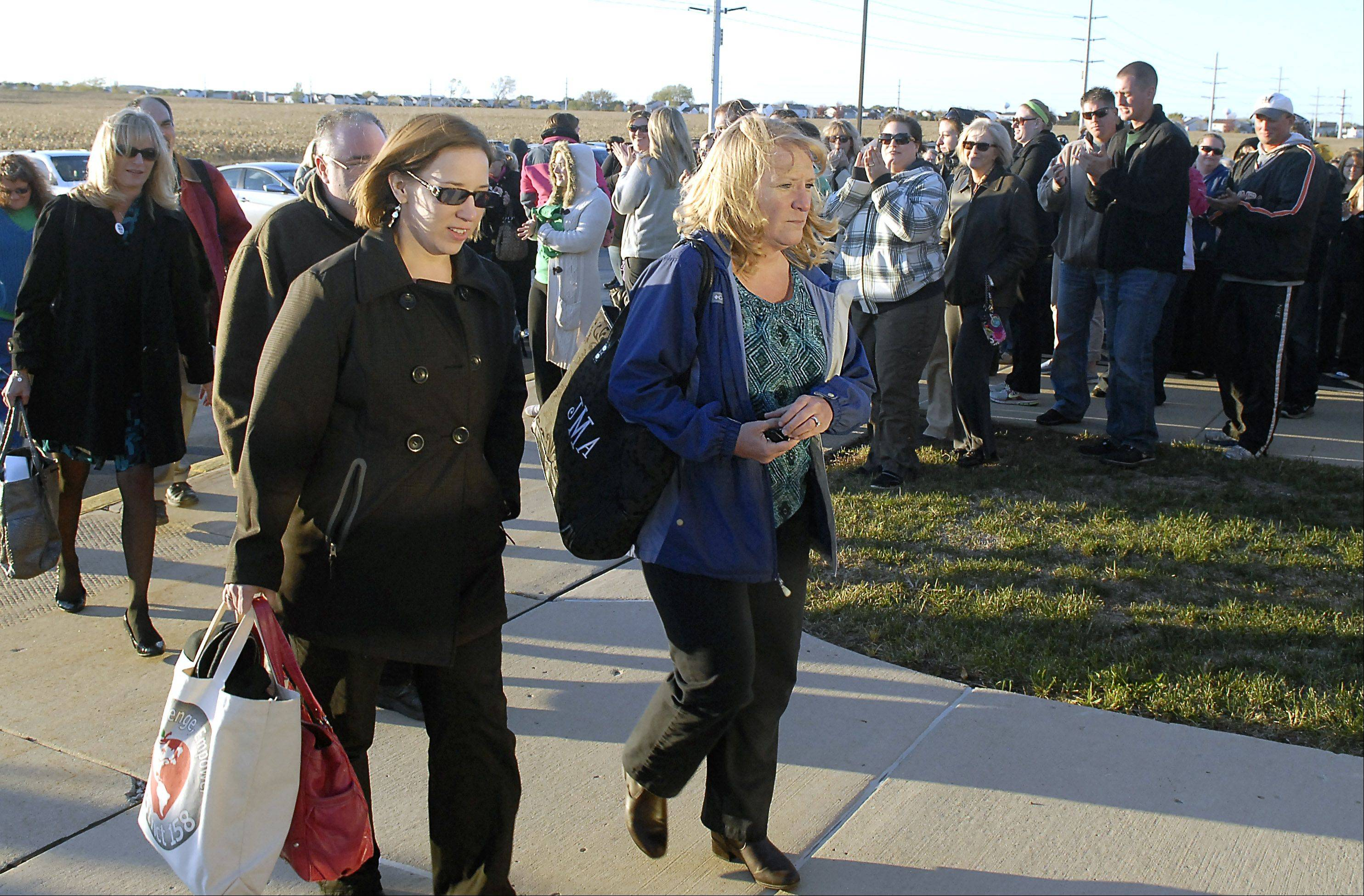 Huntley Education Association co-presidents Chris Laird, left, and Julie McLaughlin are applauded as they and other union representatives walk into Huntley Unit District 158 headquarters in Algonquin on Oct. 10 � the last time the two sides met before hammering out a tentative contract Tuesday night.