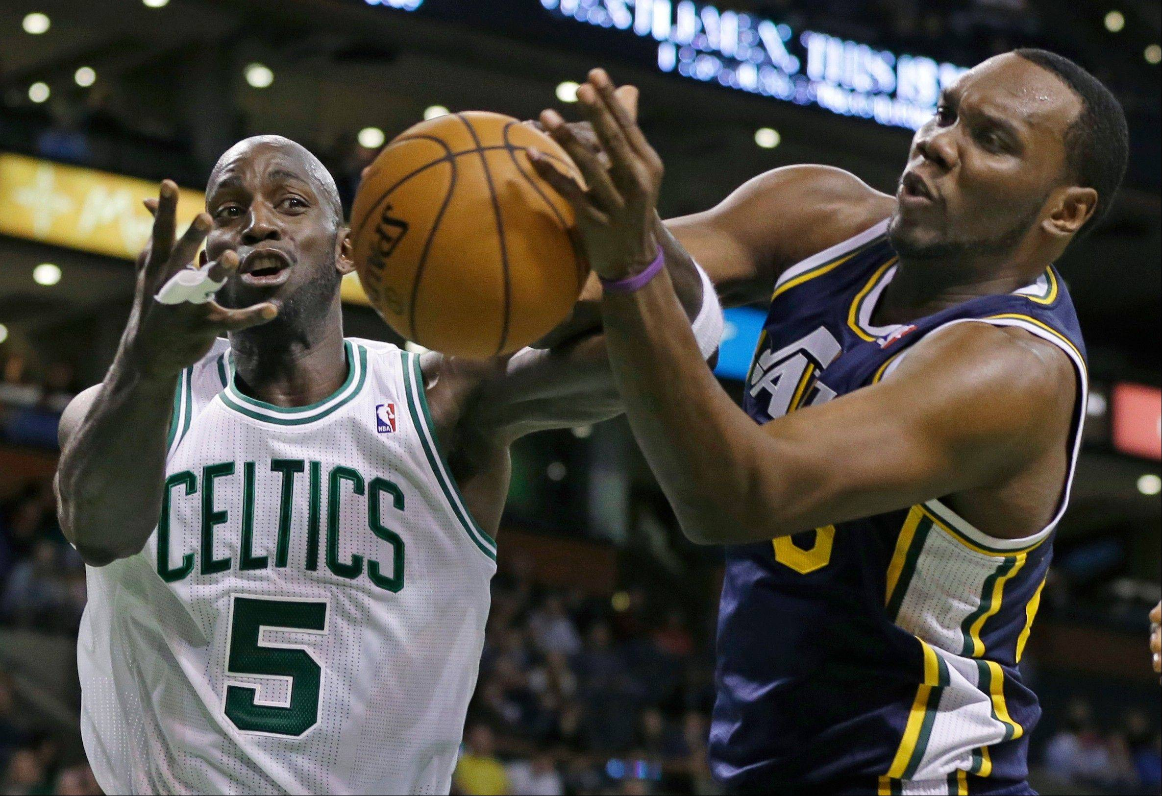 Boston Celtics power forward Kevin Garnett battles for a loose ball with Utah Jazz center Al Jefferson Wednesday during the first half in Boston.