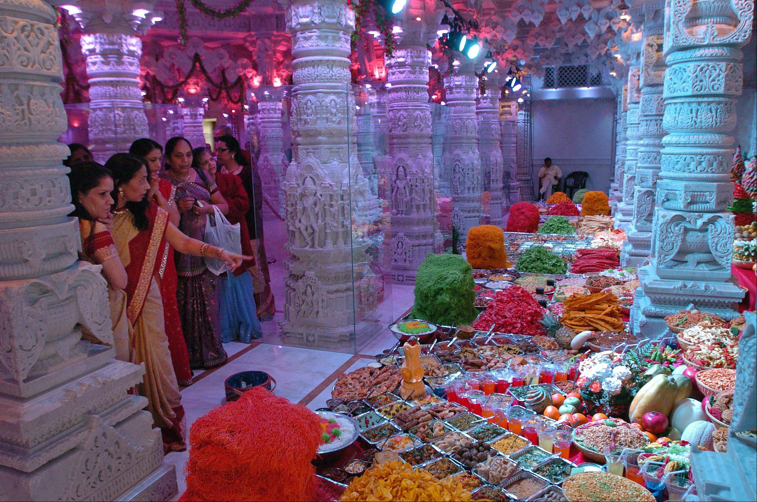 People visit the BAPS Hindu Temple in Bartlett and reflect over the annakut, or mountain of food, an offering of hundreds of vegetarian delicacies as the first meal of the Hindu New Year.