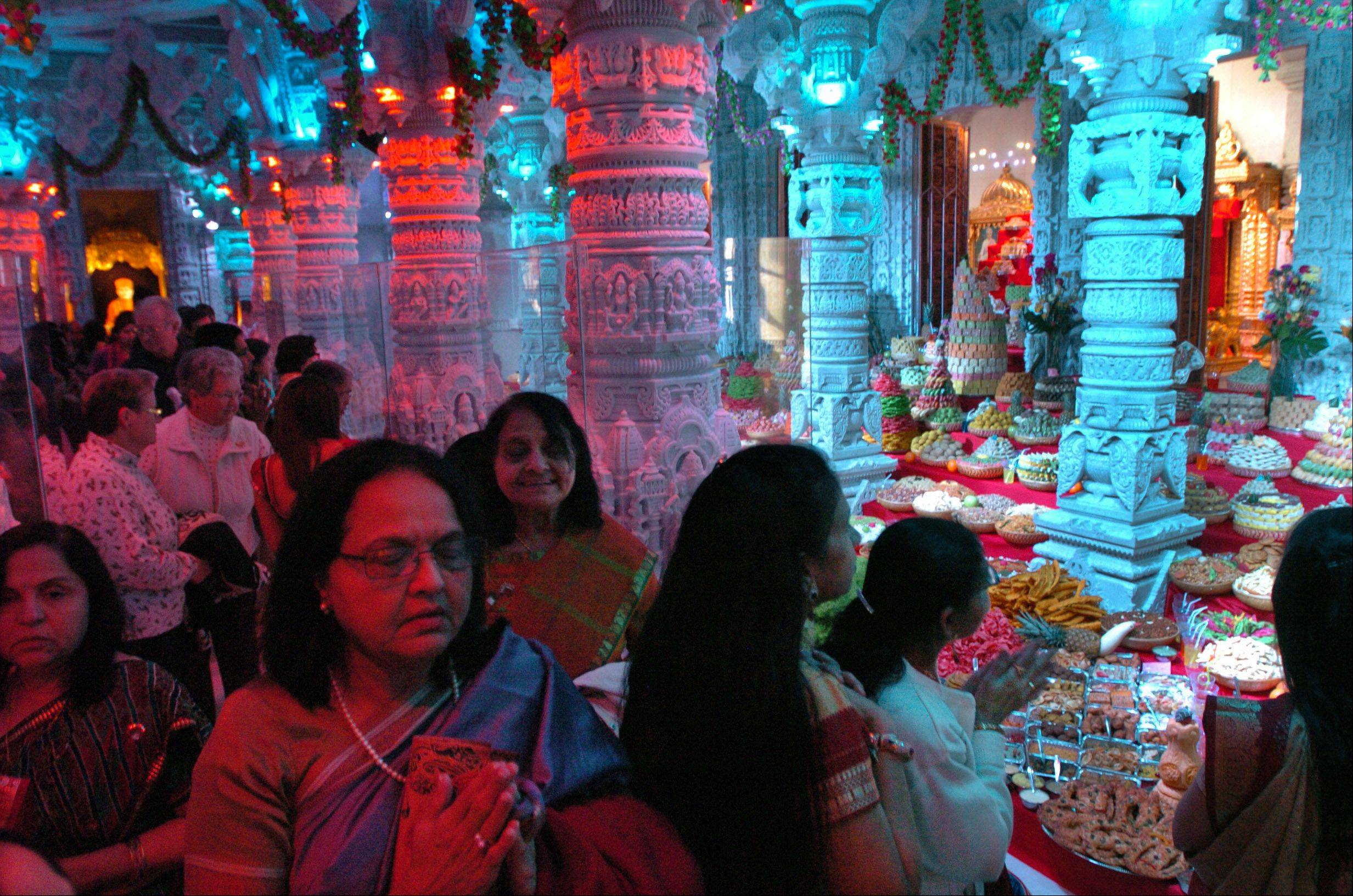 Visitors to BAPS Hindu Temple in Bartlett pass through and reflect over the annakut, or mountain of food, an offering of hundreds of vegetarian delicacies as the first meal of the Hindu New Year.