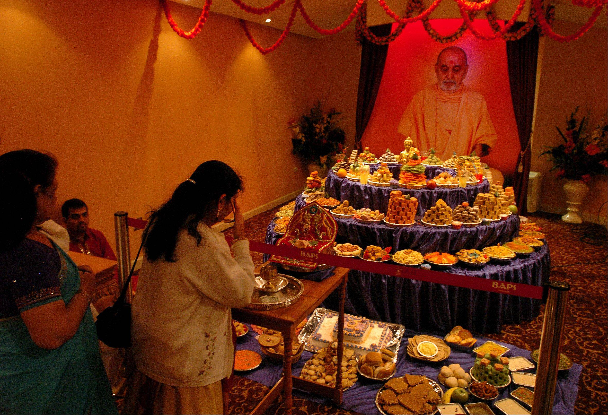 Visitors celebrate the annakut, or mountain of food, an offering of hundreds of vegetarian delicacies as the first meal of the Hindu New Year at BAPS Hindu Temple in Bartlett.