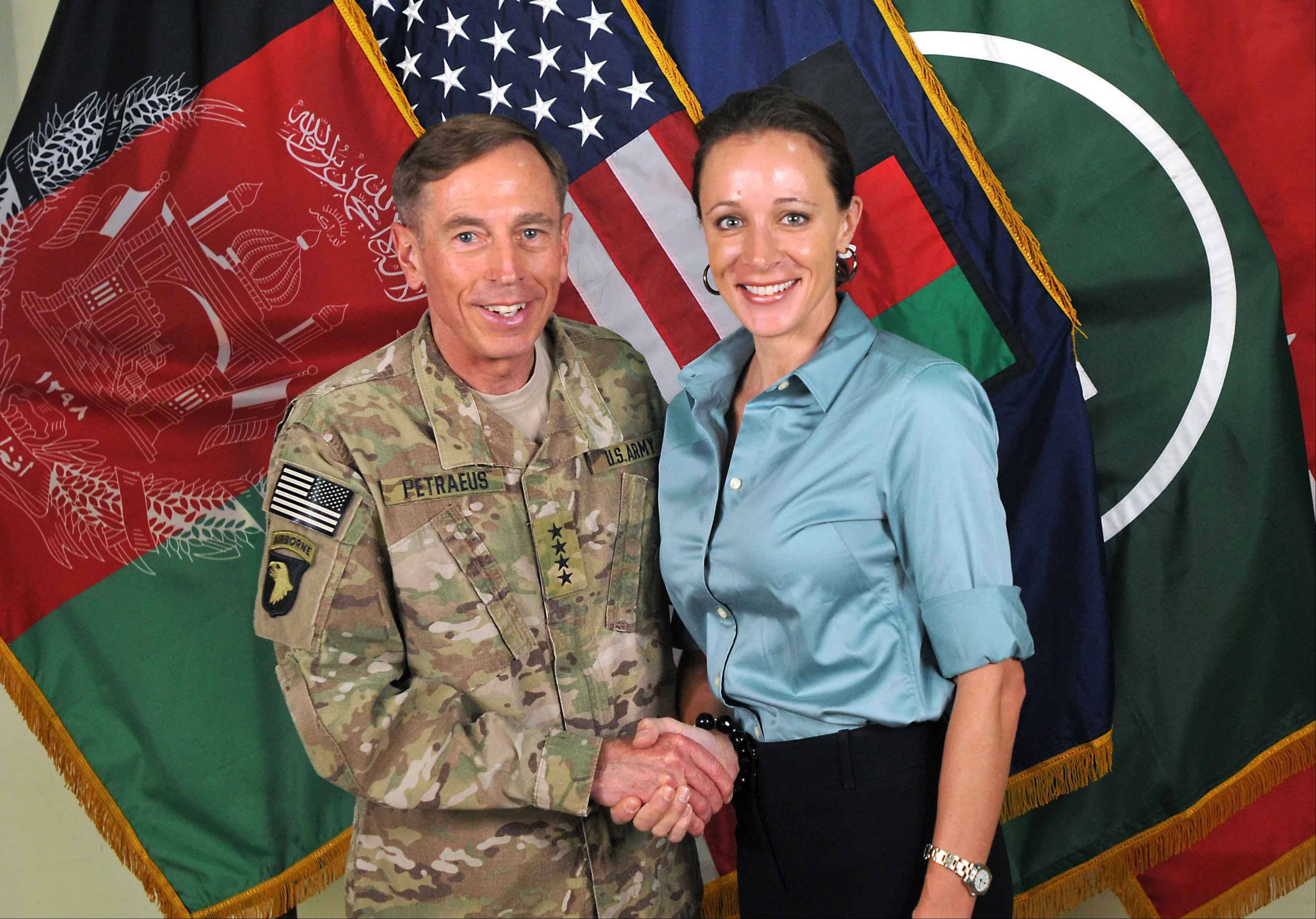 "This July 13, 2011, photo made available on the International Security Assistance Force's Flickr website shows the former Commander of International Security Assistance Force and U.S. Forces-Afghanistan Gen. David Petraeus, left, shaking hands with Paula Broadwell, co-author of ""All In: The Education of General David Petraeus."""
