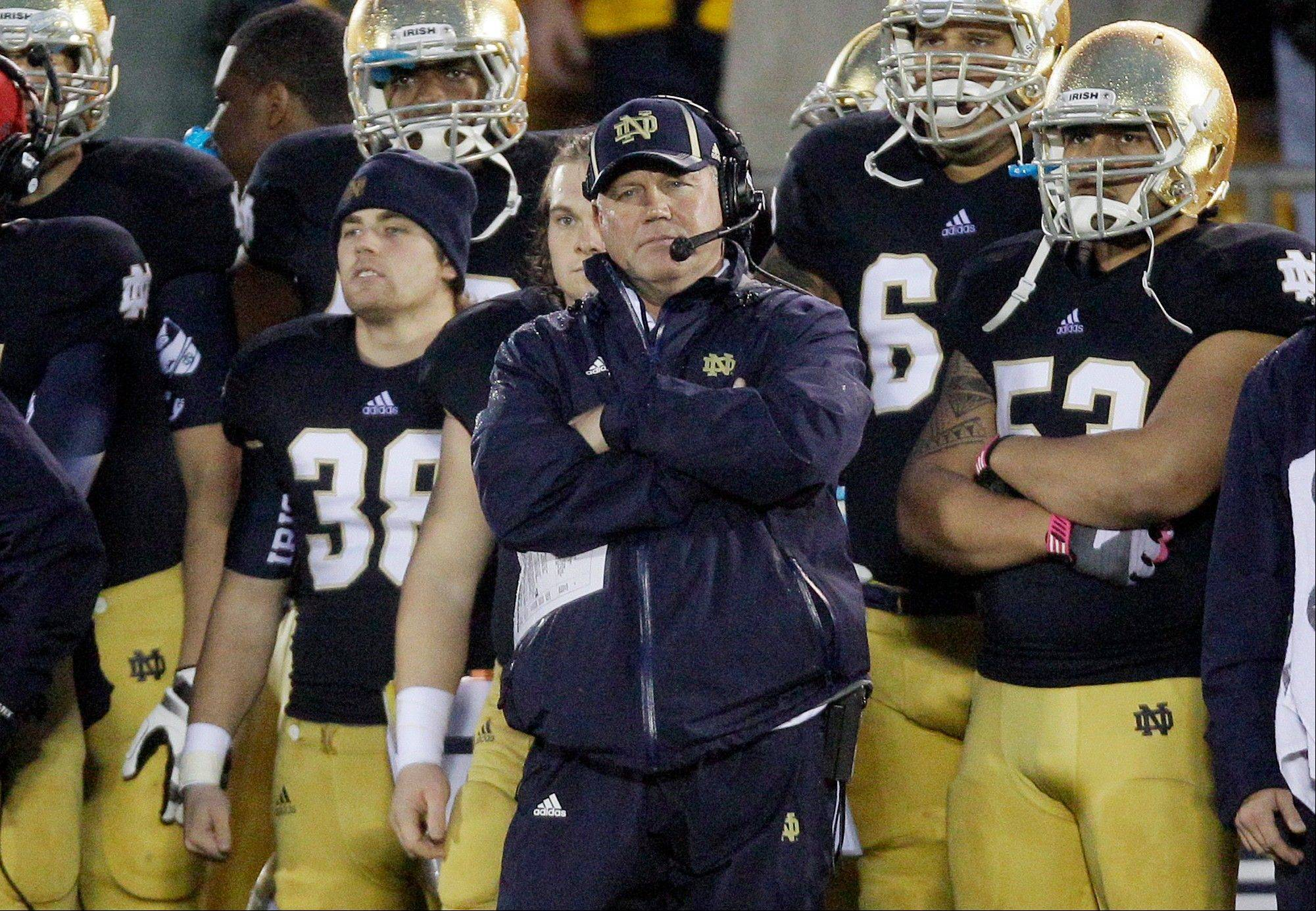 Notre Dame head coach Brian Kelly watches from the sideline during overtime of an NCAA college football game against Stanford in South Bend. Kelly says he doesn't believe third-ranked Notre Dame's season will be lessened if the Fighting Irish finish the season undefeated and don't win a national championship.